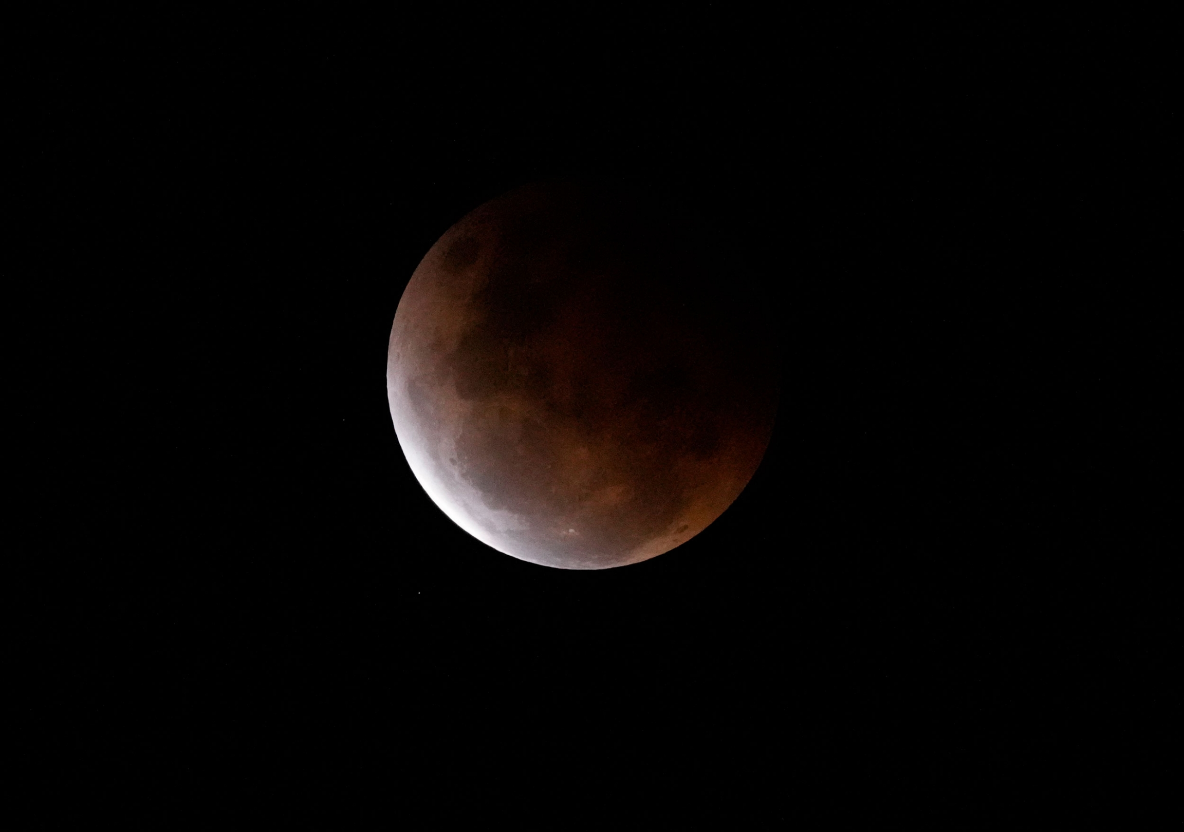 The super blood moon shown with the sun's orange colors reflected on the surface.