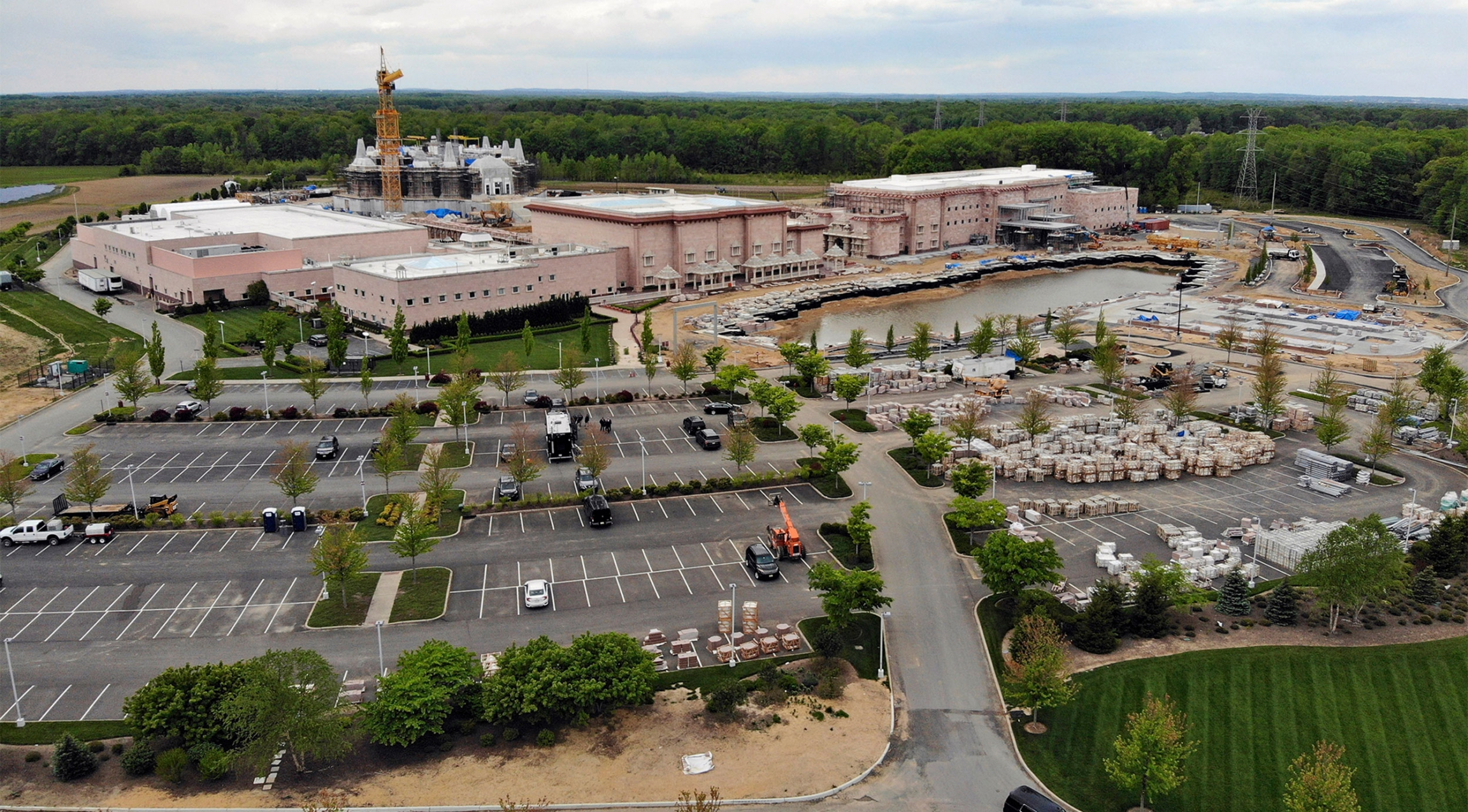 Aerial view of a Hindu temple next to a parking lot and greenery.