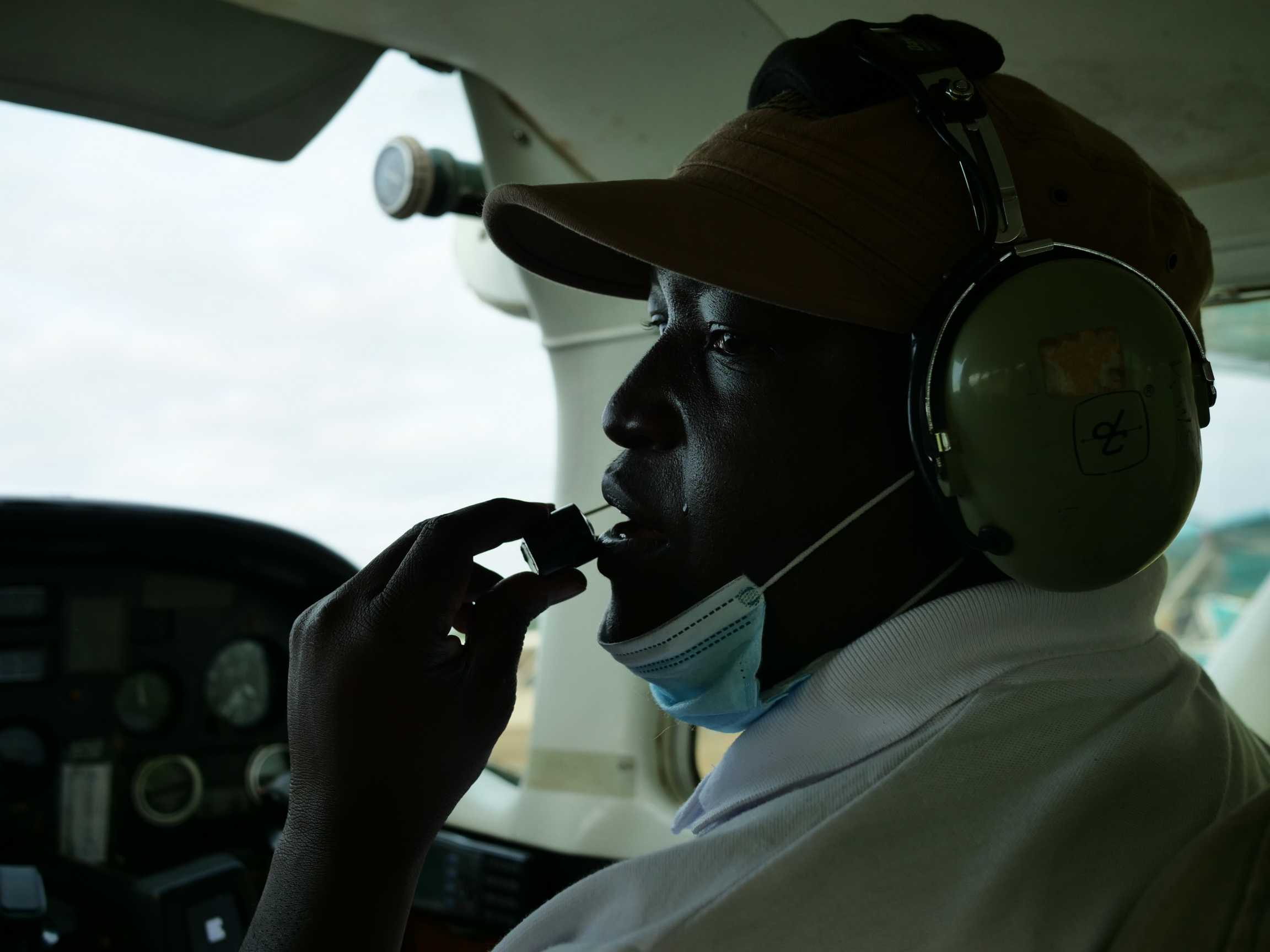 Man in a plane cockpit wearing a hat and headphones speaking into an audio transmitter