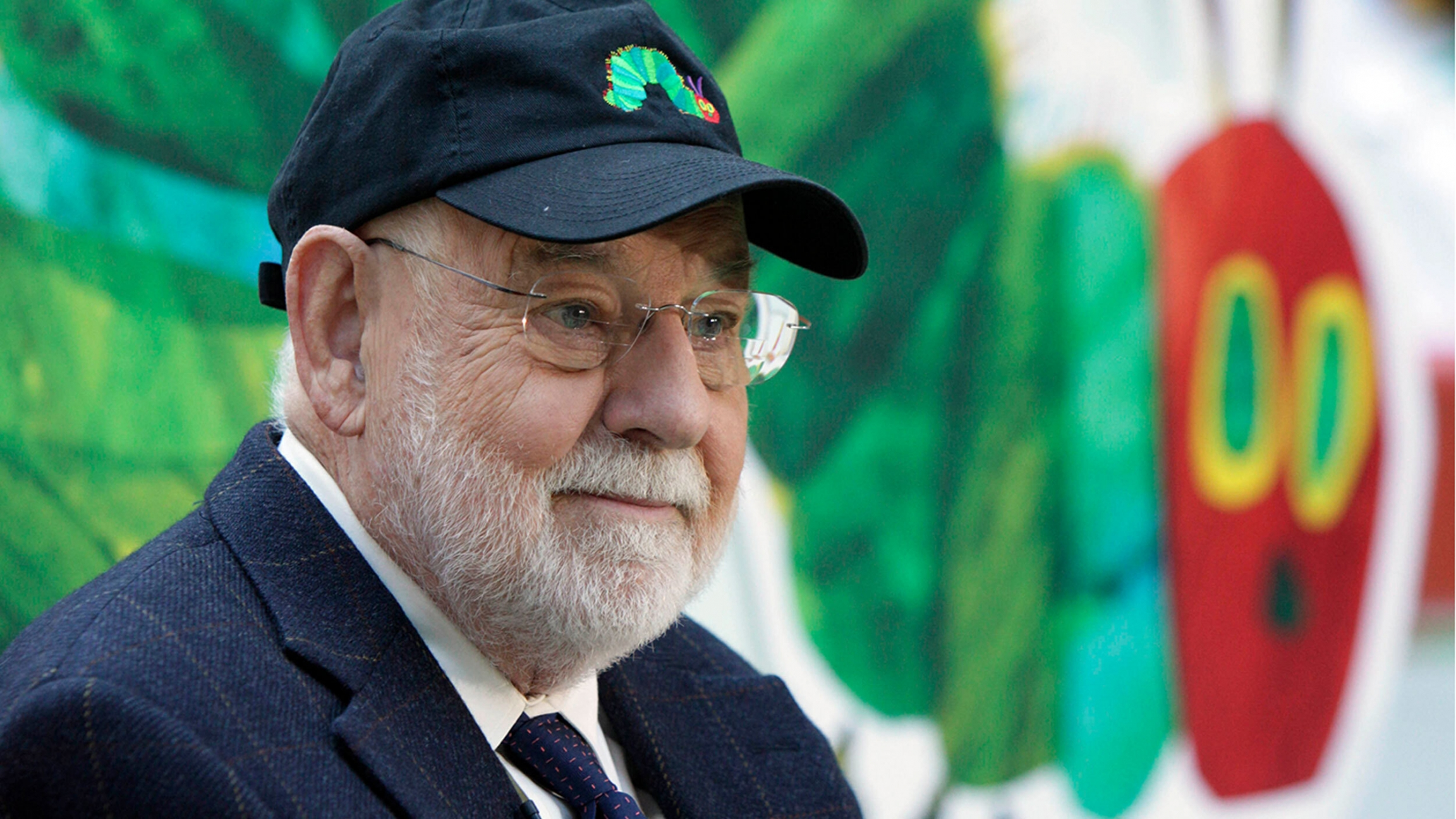 Author Eric Carle is shown with a white beard and warding a suit, tie and baseball hat.