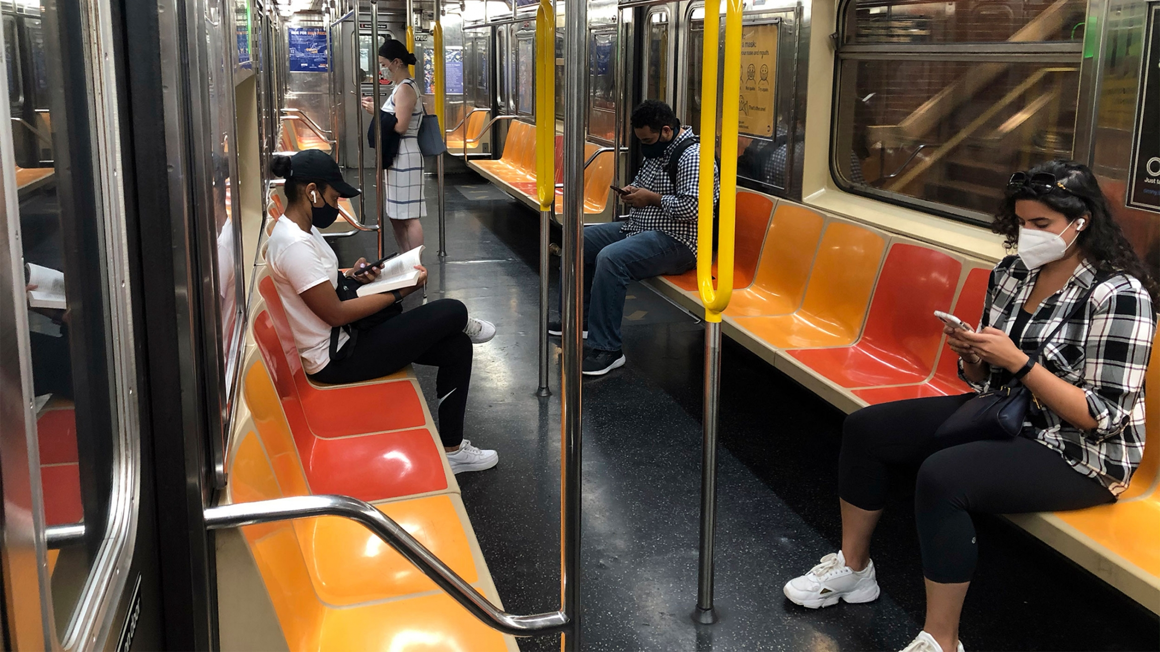 People wearing different types of black and white clothes sit and stand among orange and yellow seats on the New York subway