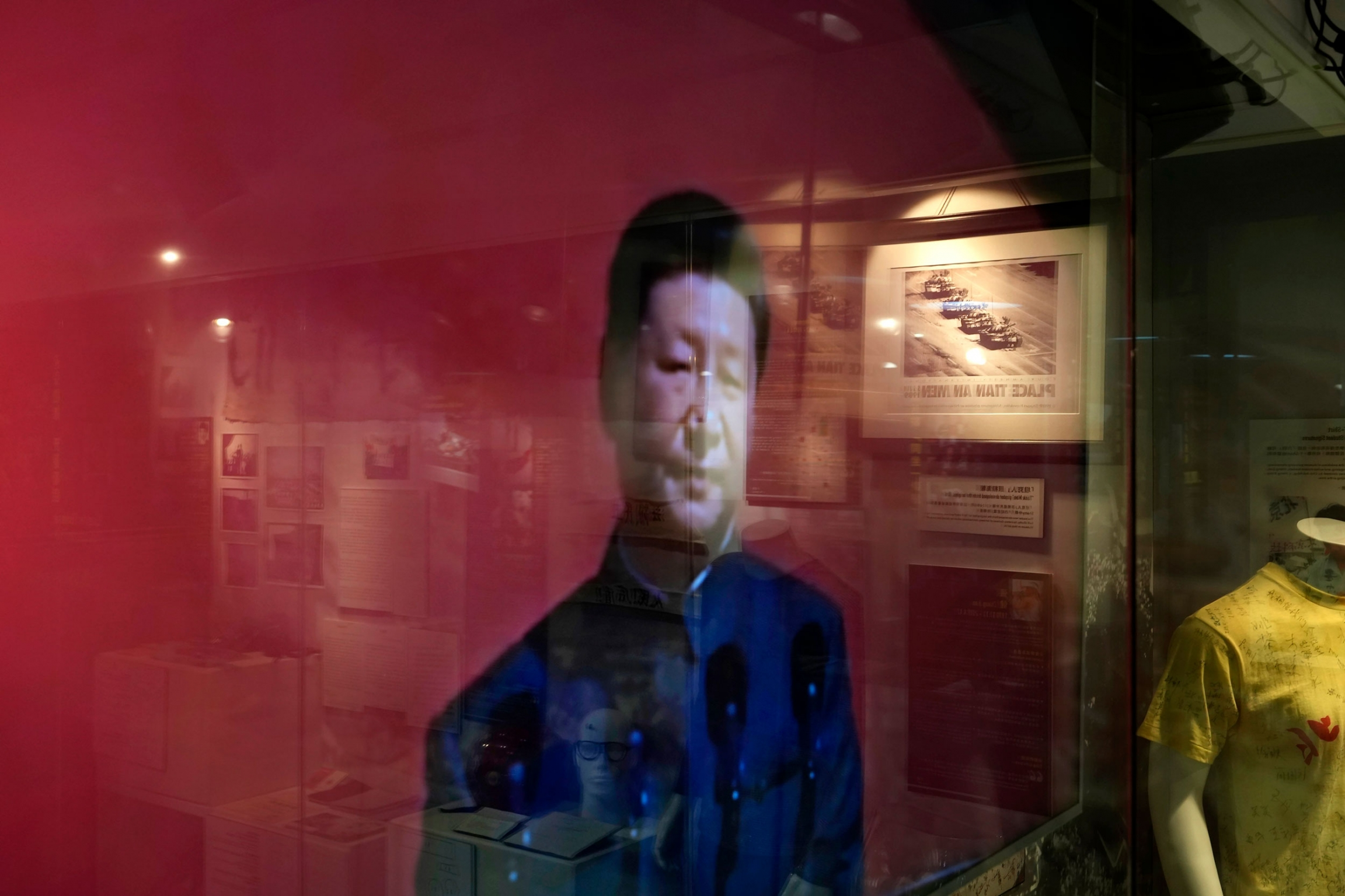An image of China President Xi Jinping depicted on a red background is shown is shown through glass that's reflecting other Tiananmen Square artifacts.