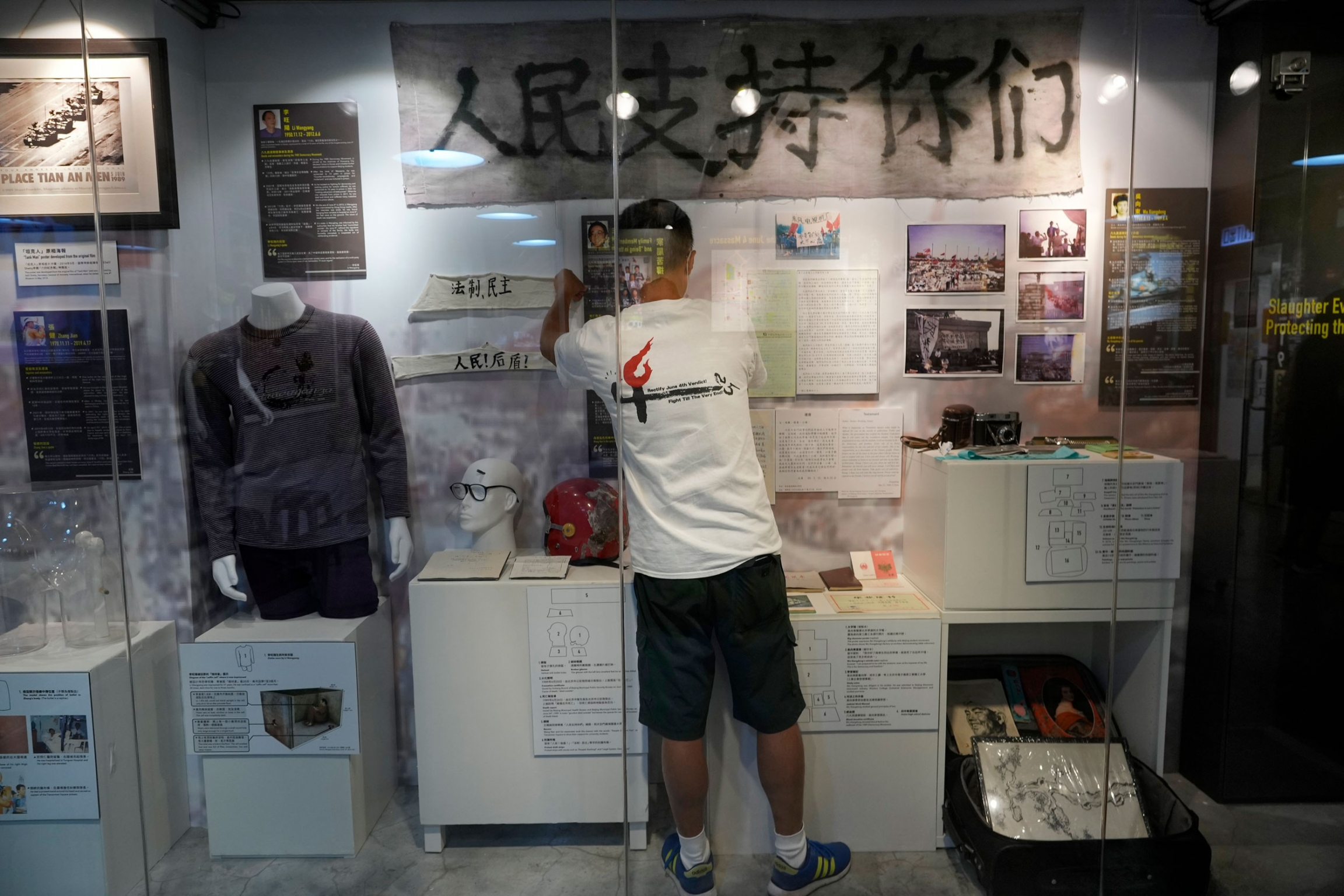 A man is shown wearing shorts and a t-shirt and standing in front of Tiananmen Square artifacts both hanging on the wall and on a mannequin.