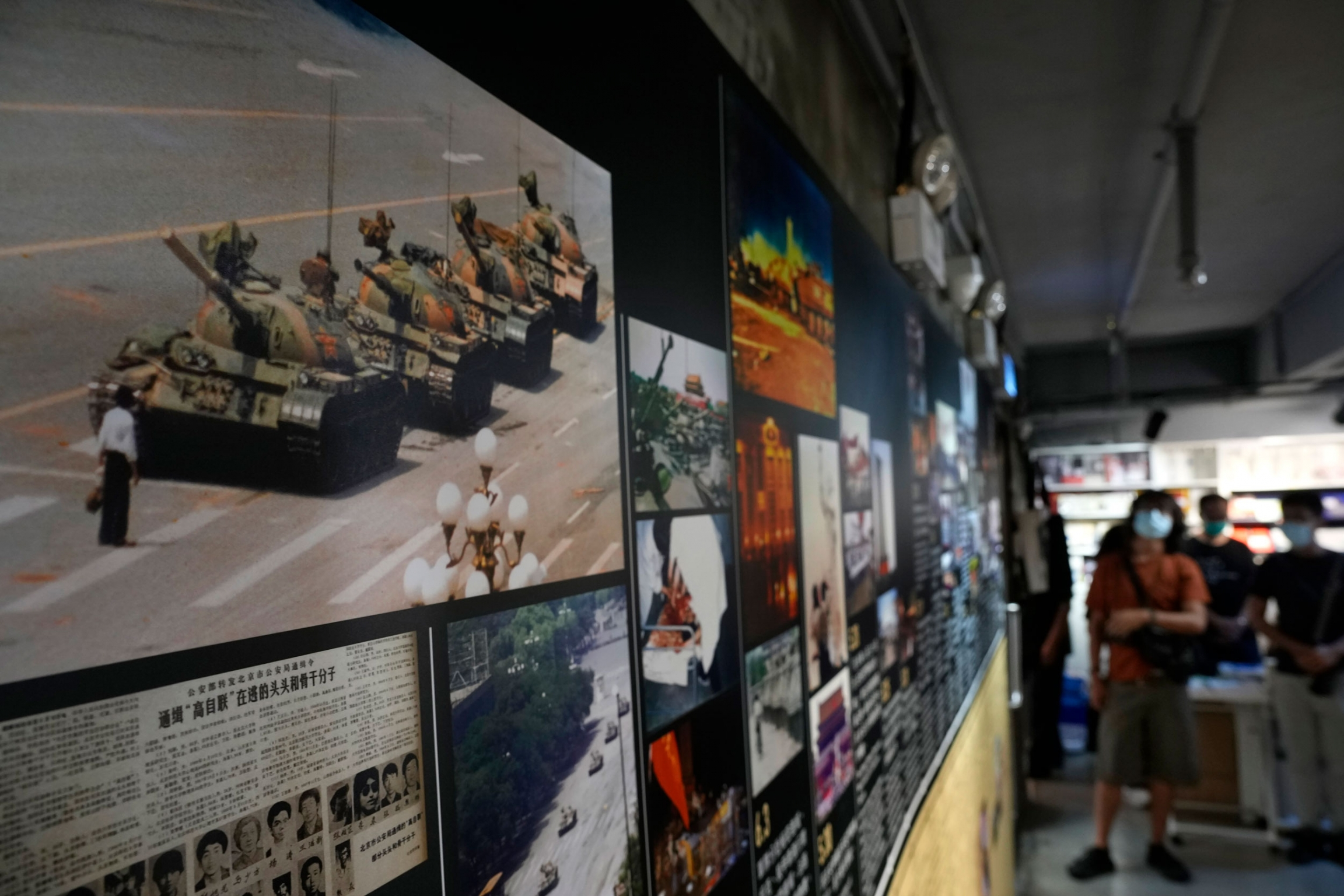 A photograph of a man blocking a line of four tanks in a street is shown hanging with other photographs and newspaper clippings.