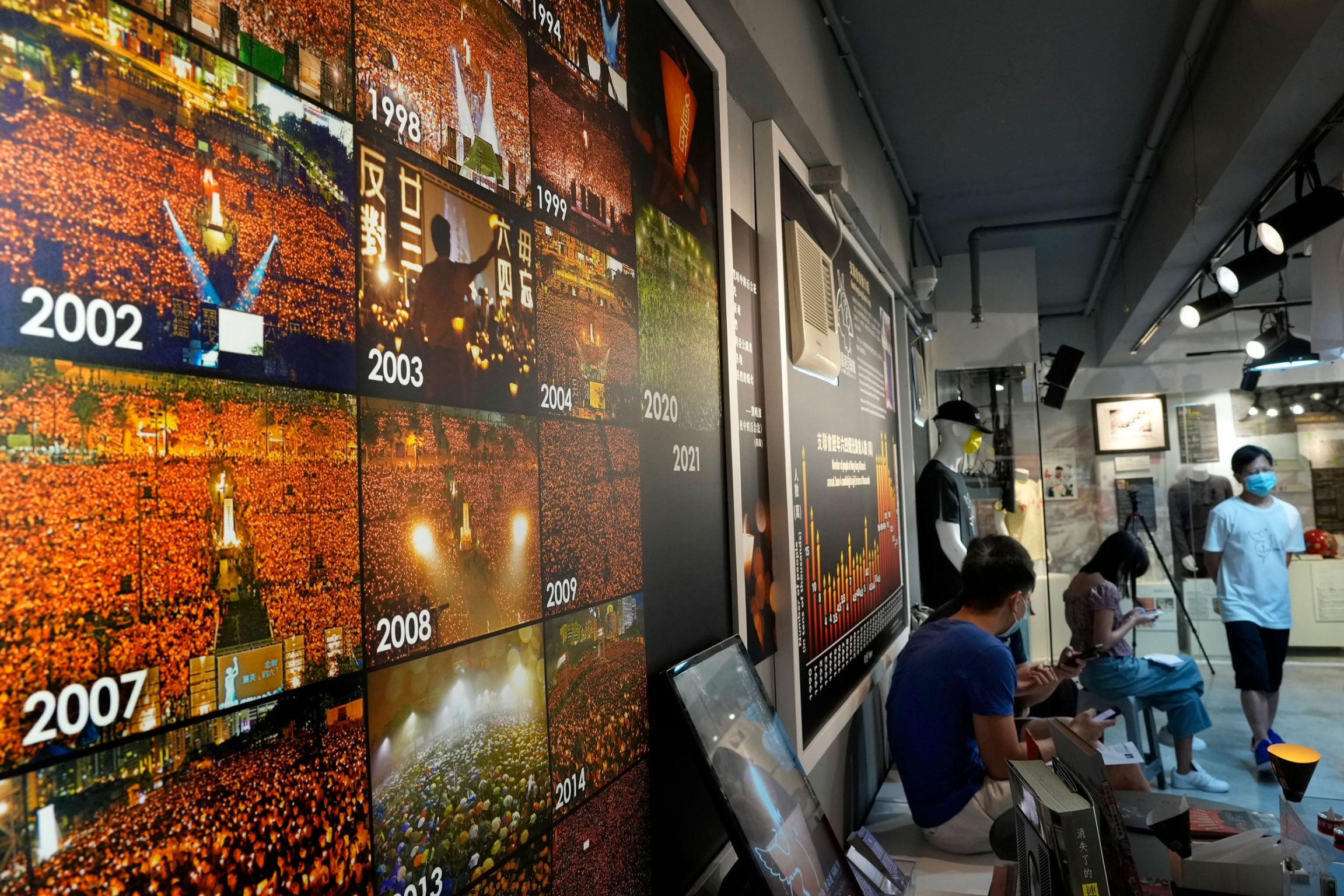 A wall of photographs showing hundreds of people gathered and holding up lit candles.
