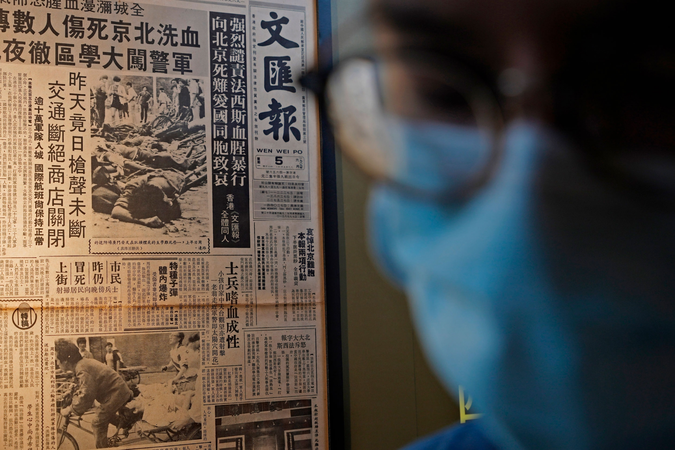 A newspaper clipping is shown in the background with a person in the near ground wearing a facemask and glasses is shown in blurred focus.