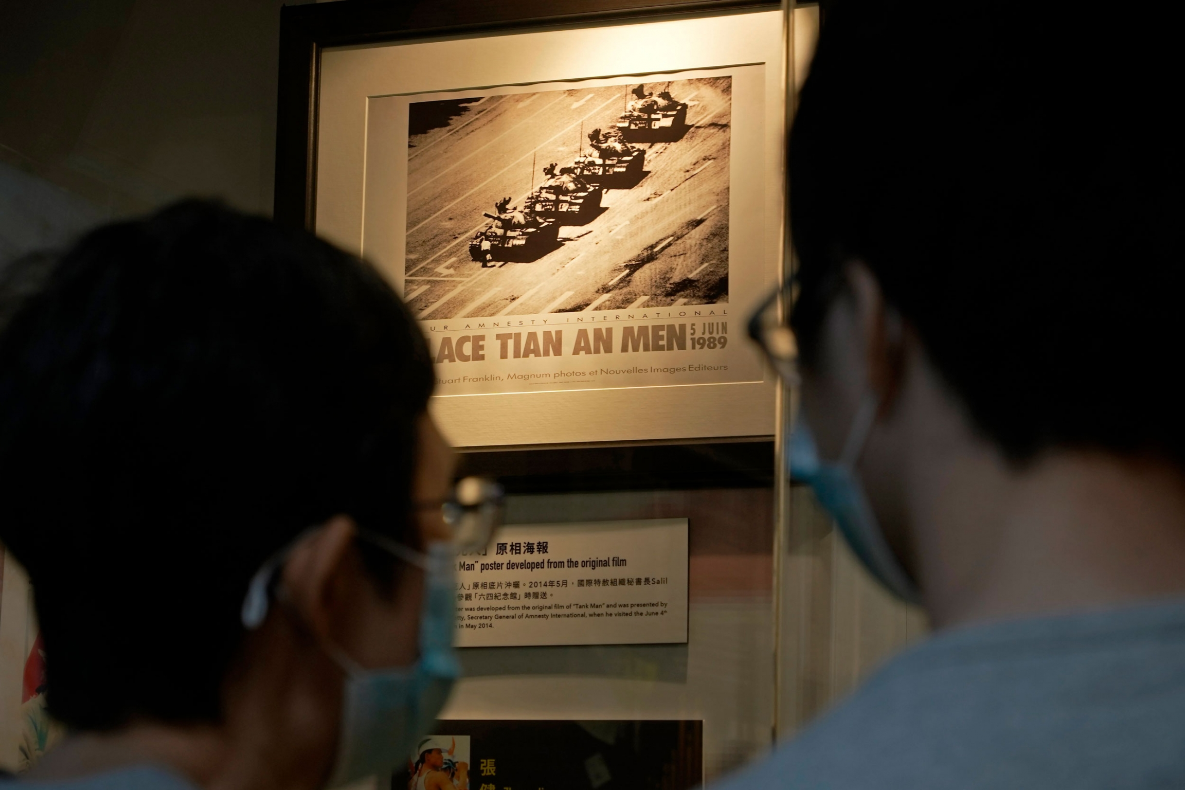 Two people are shown wearing protective face masks and looking at a photograph of a man blocking a row of four tanks.
