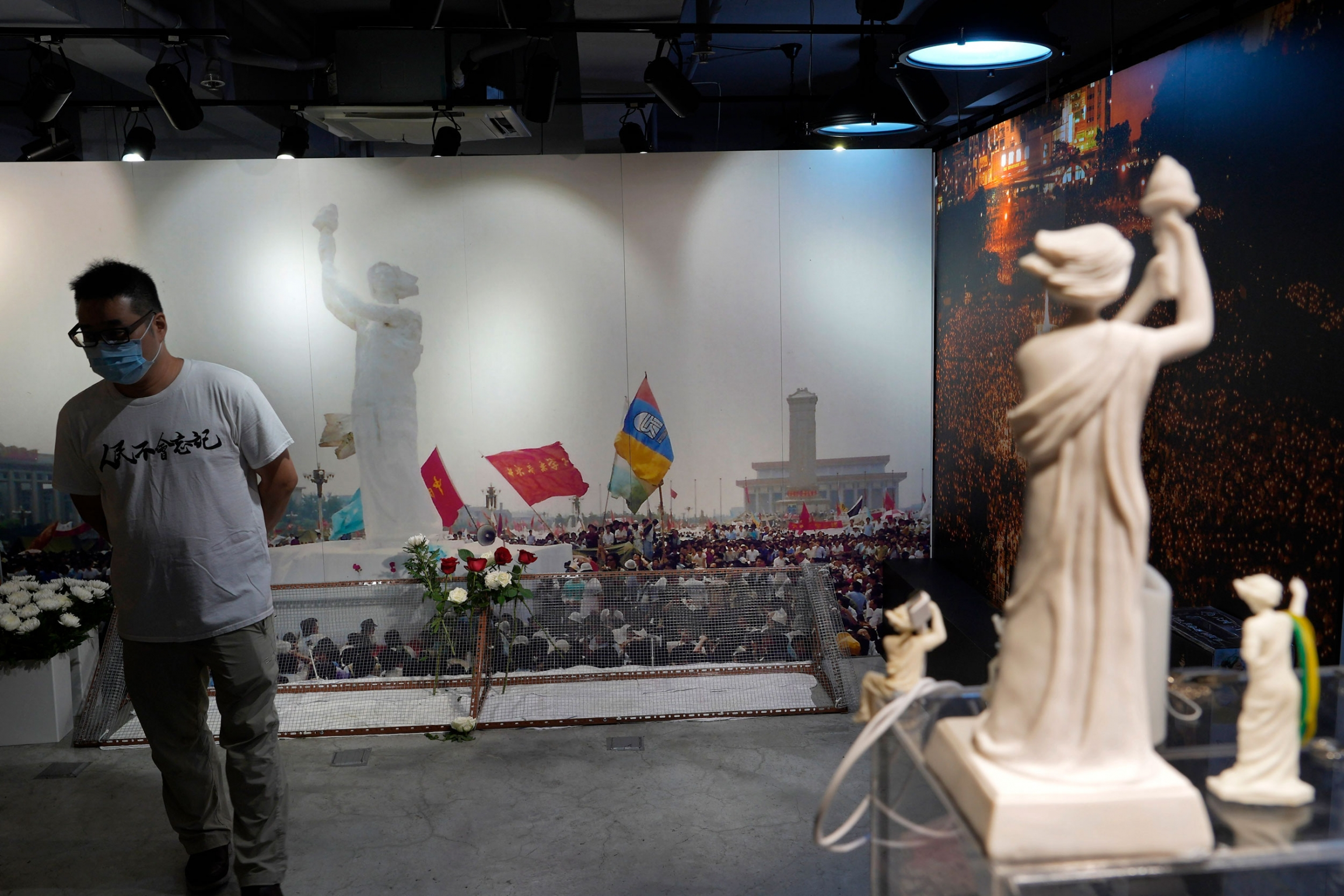 A man is shown wearing a white t-shirt, face mask and glasses while standing in front of a large wall-sized photograph depicting the Goddess of Democracy statue.