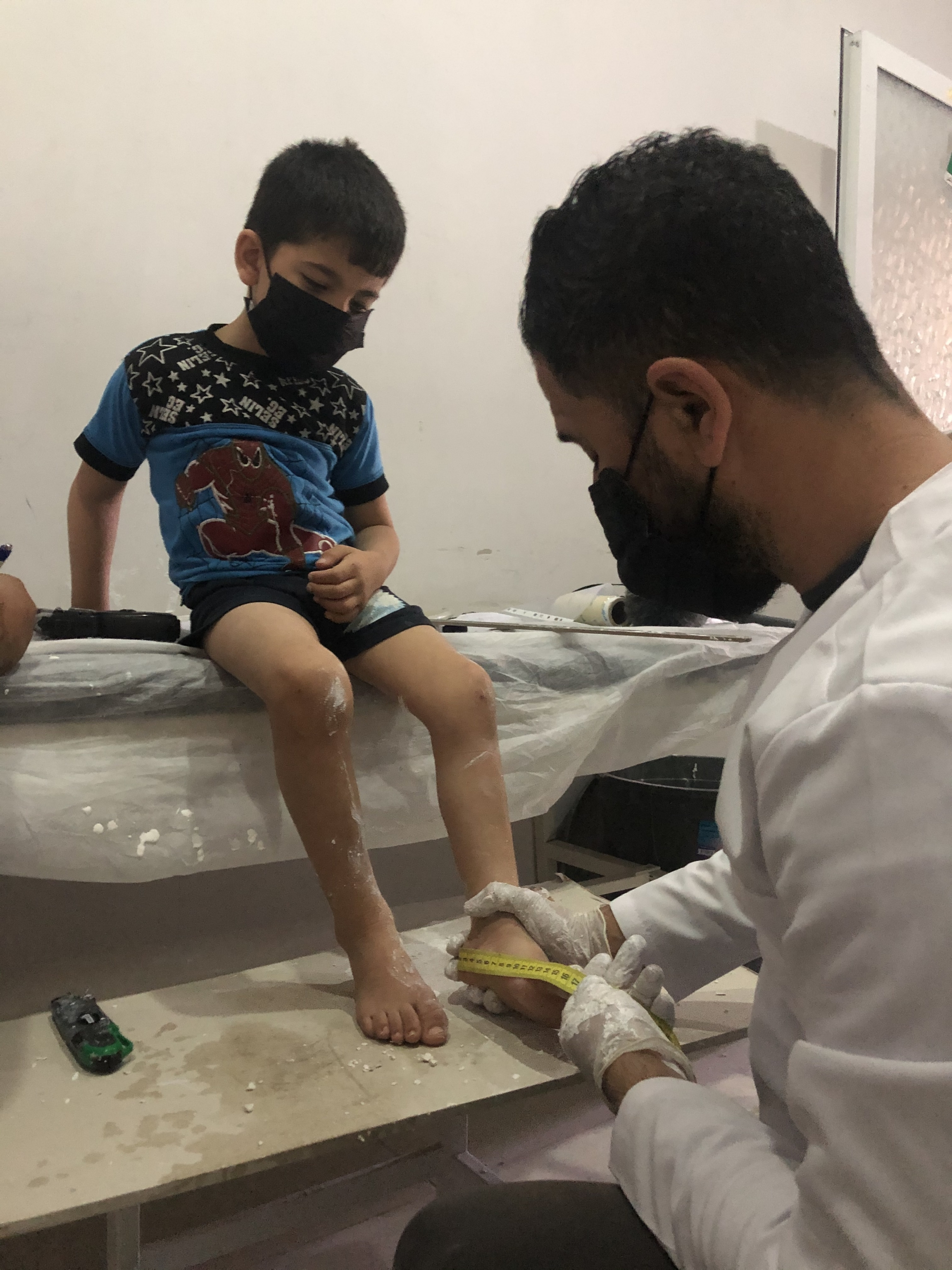 Five-year-old Jad al-Aweis suffers from cerebral palsy due to lack of oxygen at birth. Here, a specialist at a prosthetic limbs center in Turkey takes measurements of his legs so he can make braces that will help Jad walk.