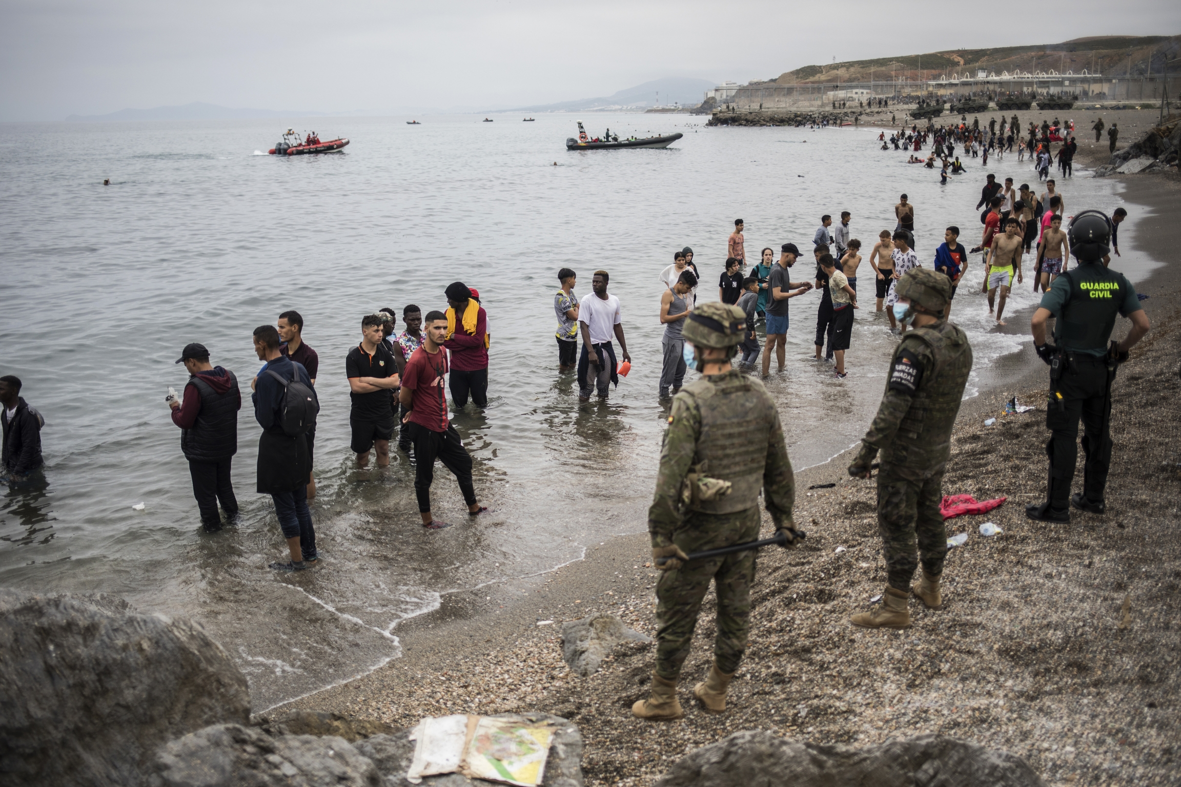 People mainly from Morocco stand on the shore as the Spanish Army cordons off the area at the border of Morocco and Spain, at the Spanish enclave of Ceuta, May 18, 2021.