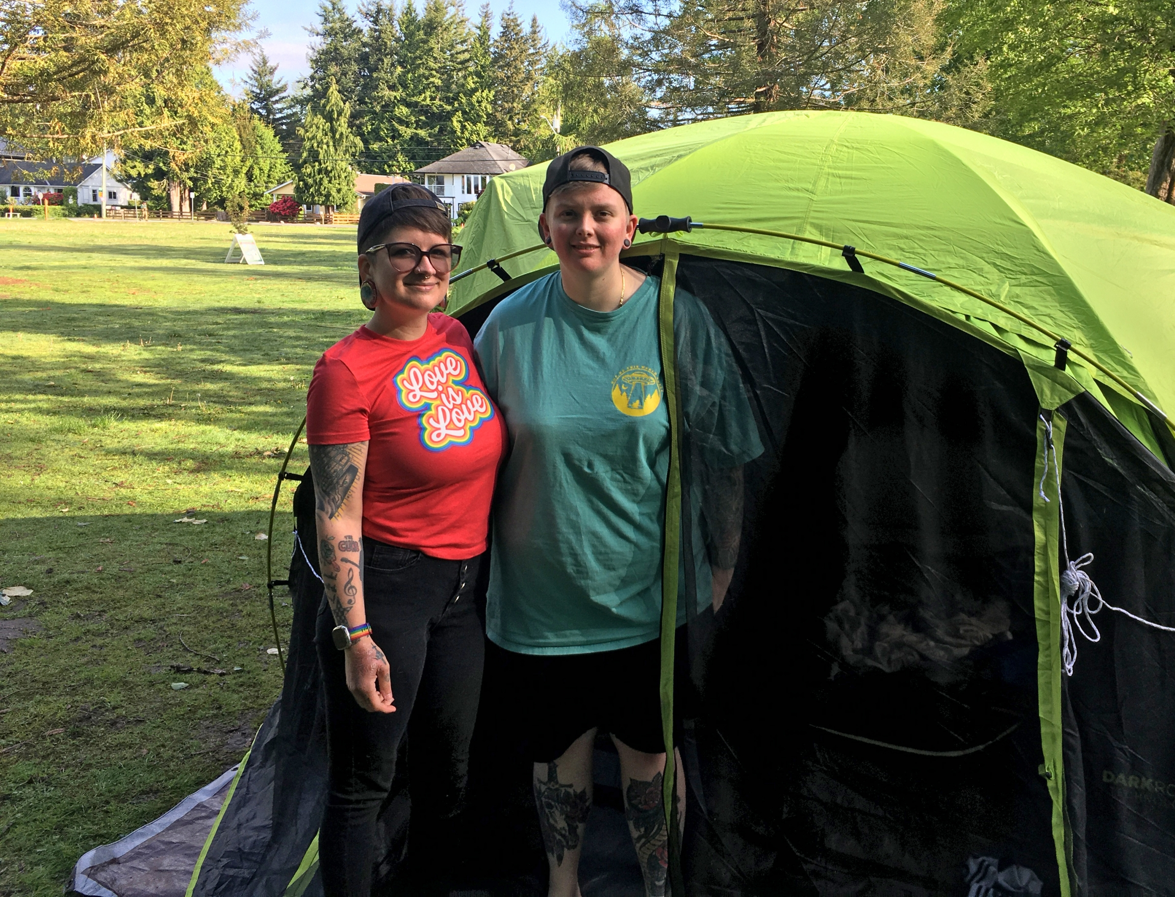 Alexis Gurr (left), of Everett, Washington, and her wife, Katrina Gurr, of Port Moody, British Columbia, pose outside their tent on the USside of Peace Arch Park.