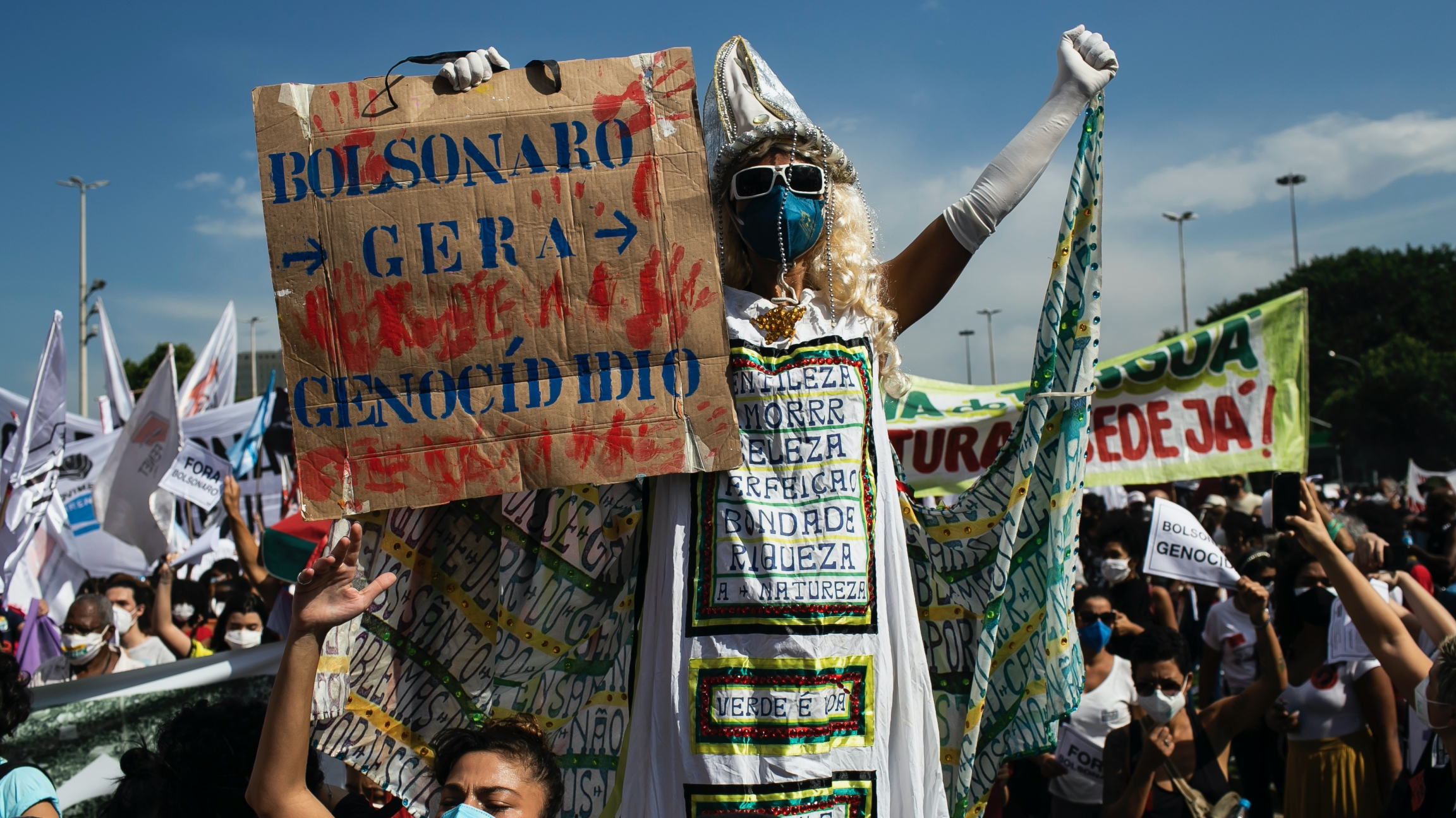"""A man walking on stilts holds a sign with a message that reads in Portuguese: """"Bolsonaro generates genocide"""""""