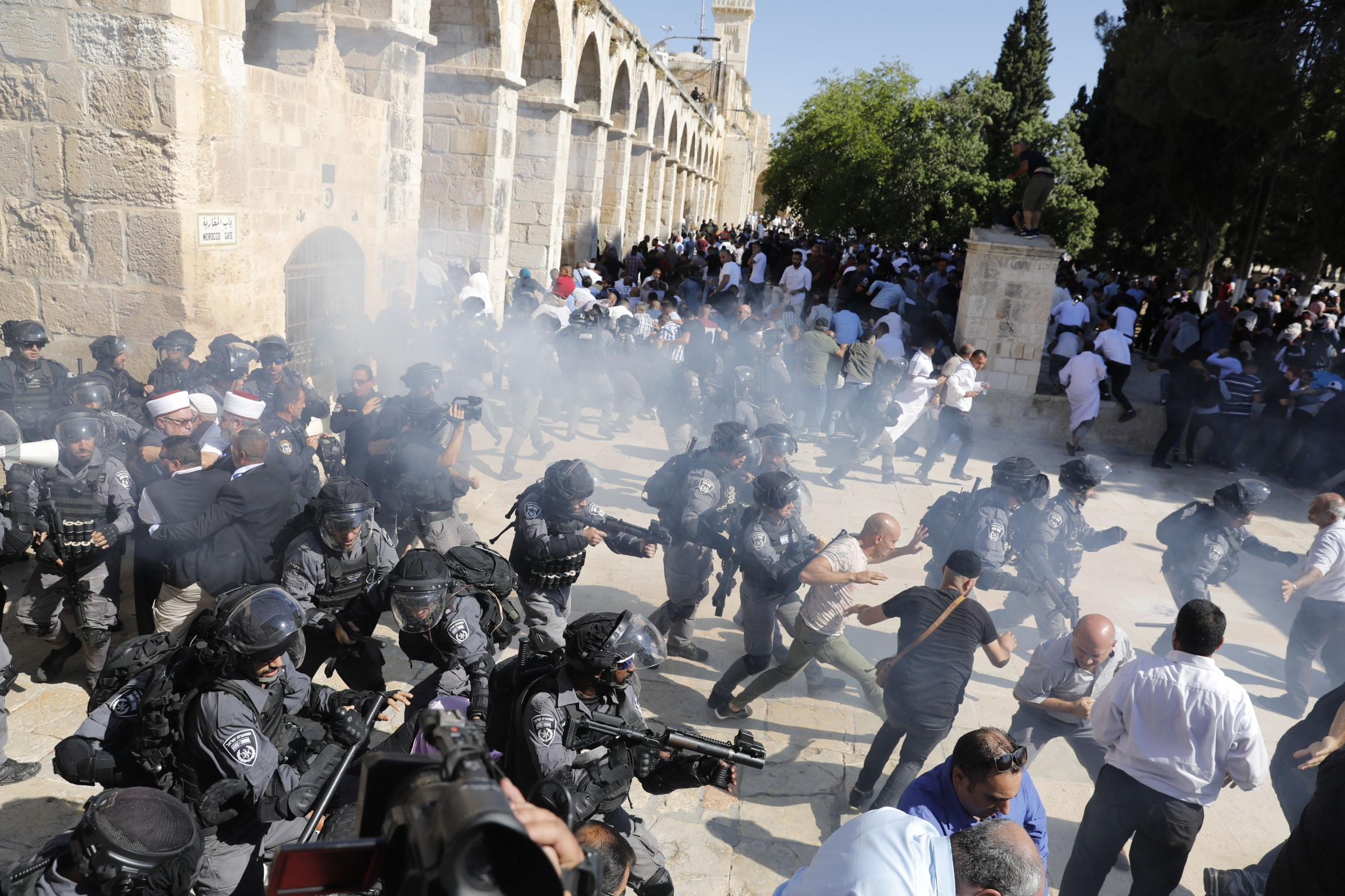 Israeli security forces firing grenades at a crowd of protesters