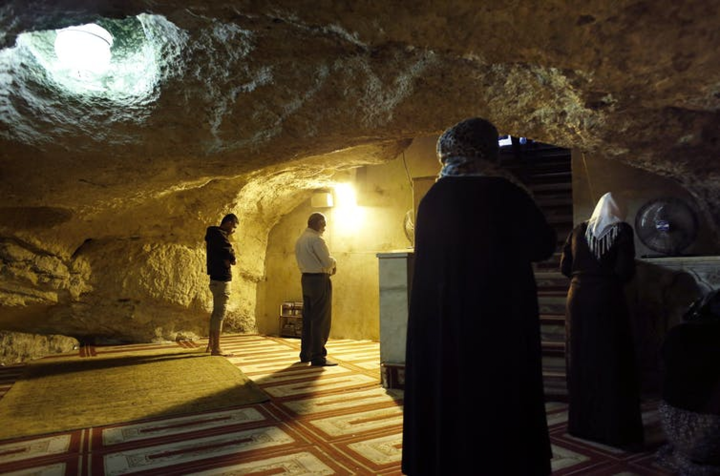 Several Muslims pray facing Mecca before a rough-stone niche in the wall