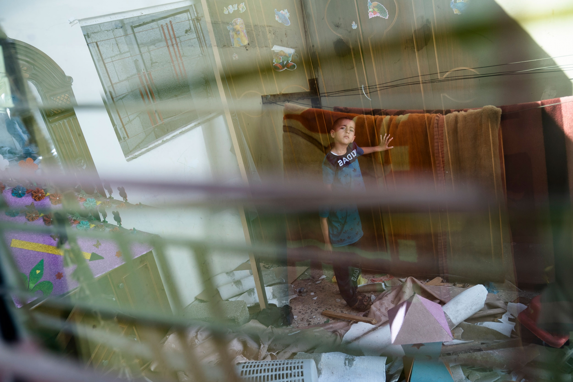 A young boy is shown standing with his hand on a blanked and seen through a window.
