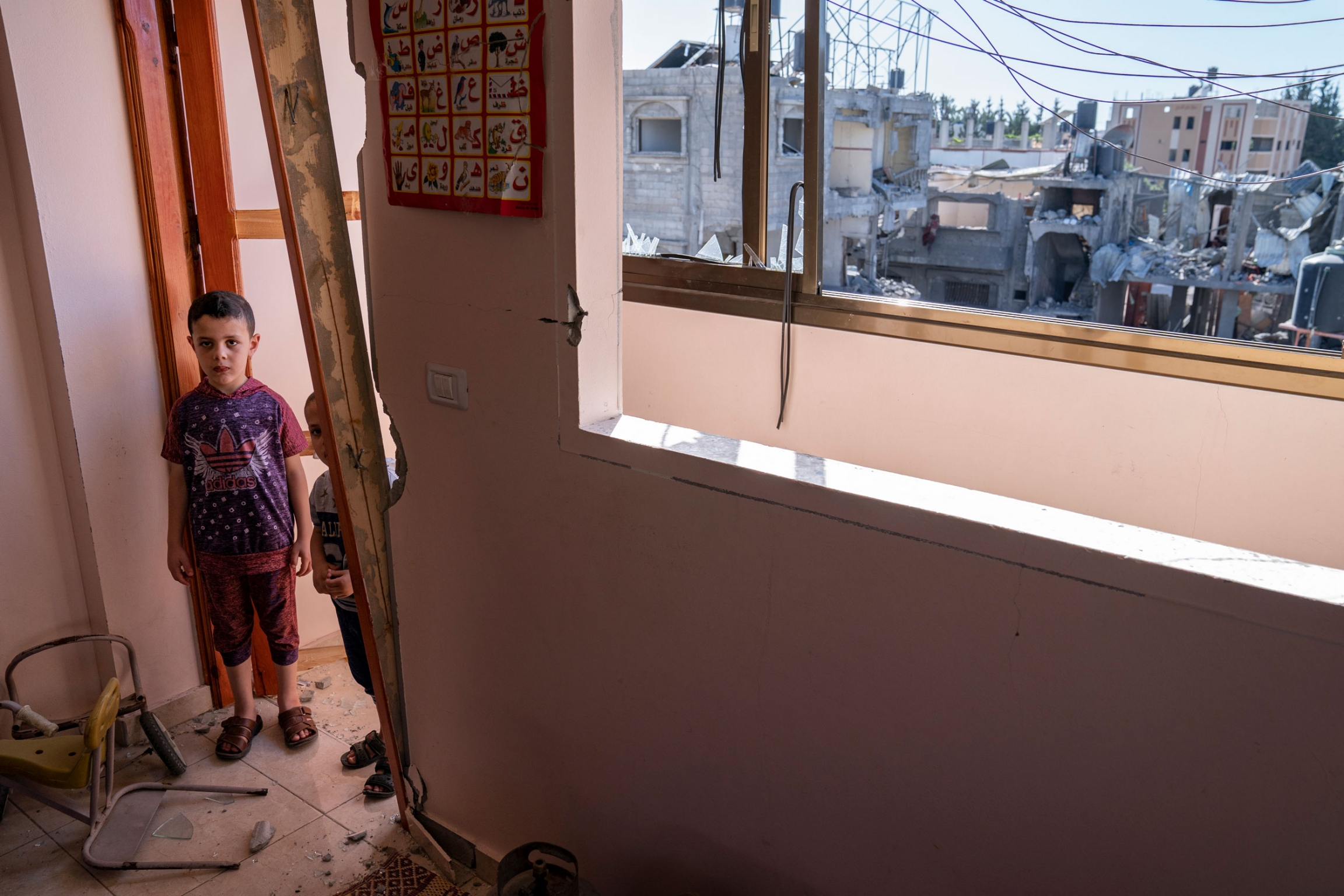 Two young boys are shown standing in a damaged door frame.