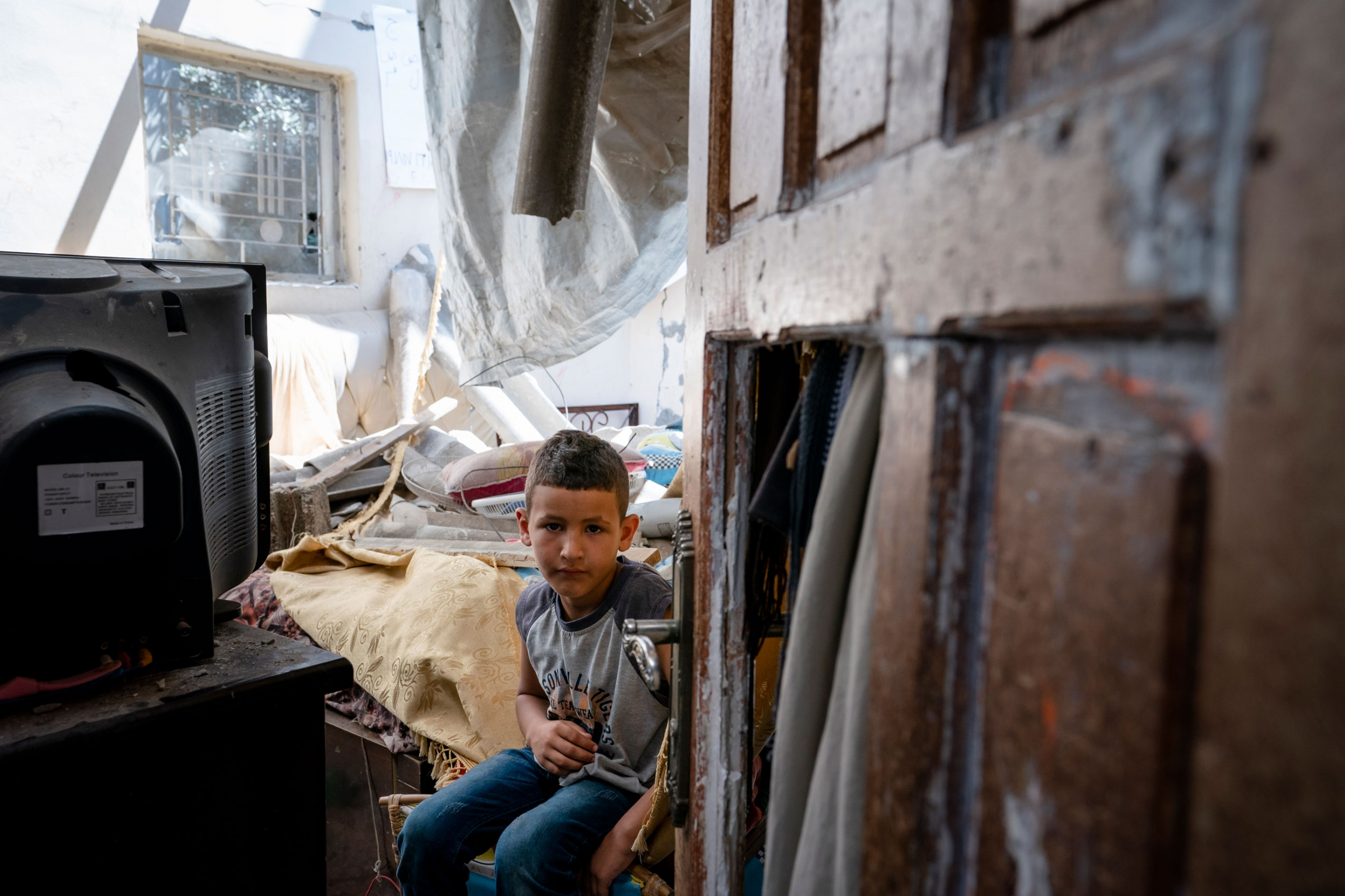 A young boy is shown seated next to a television and a damaged door in the near ground.