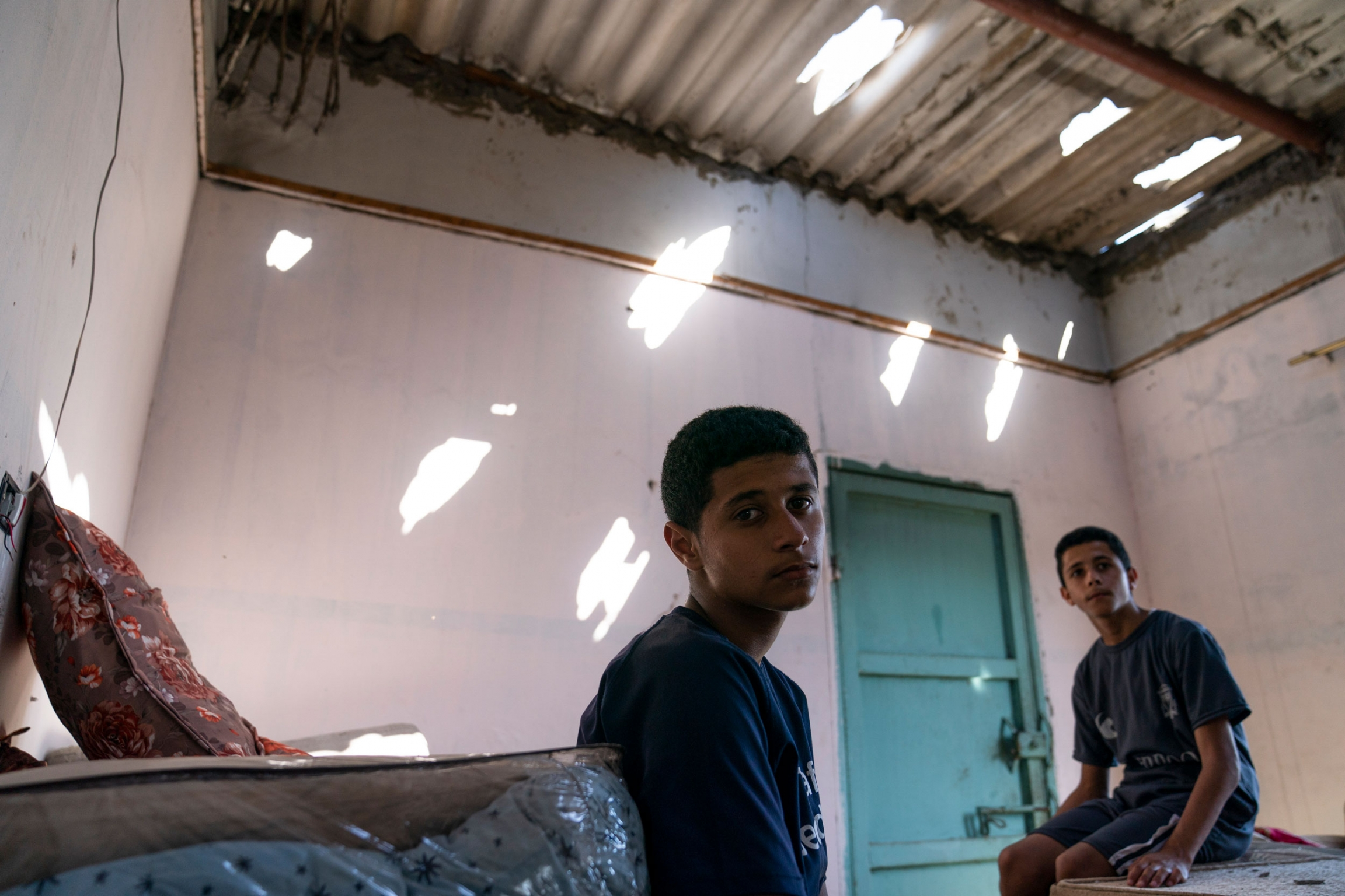 Two teenage boys sit in a room with holes in the cealing.
