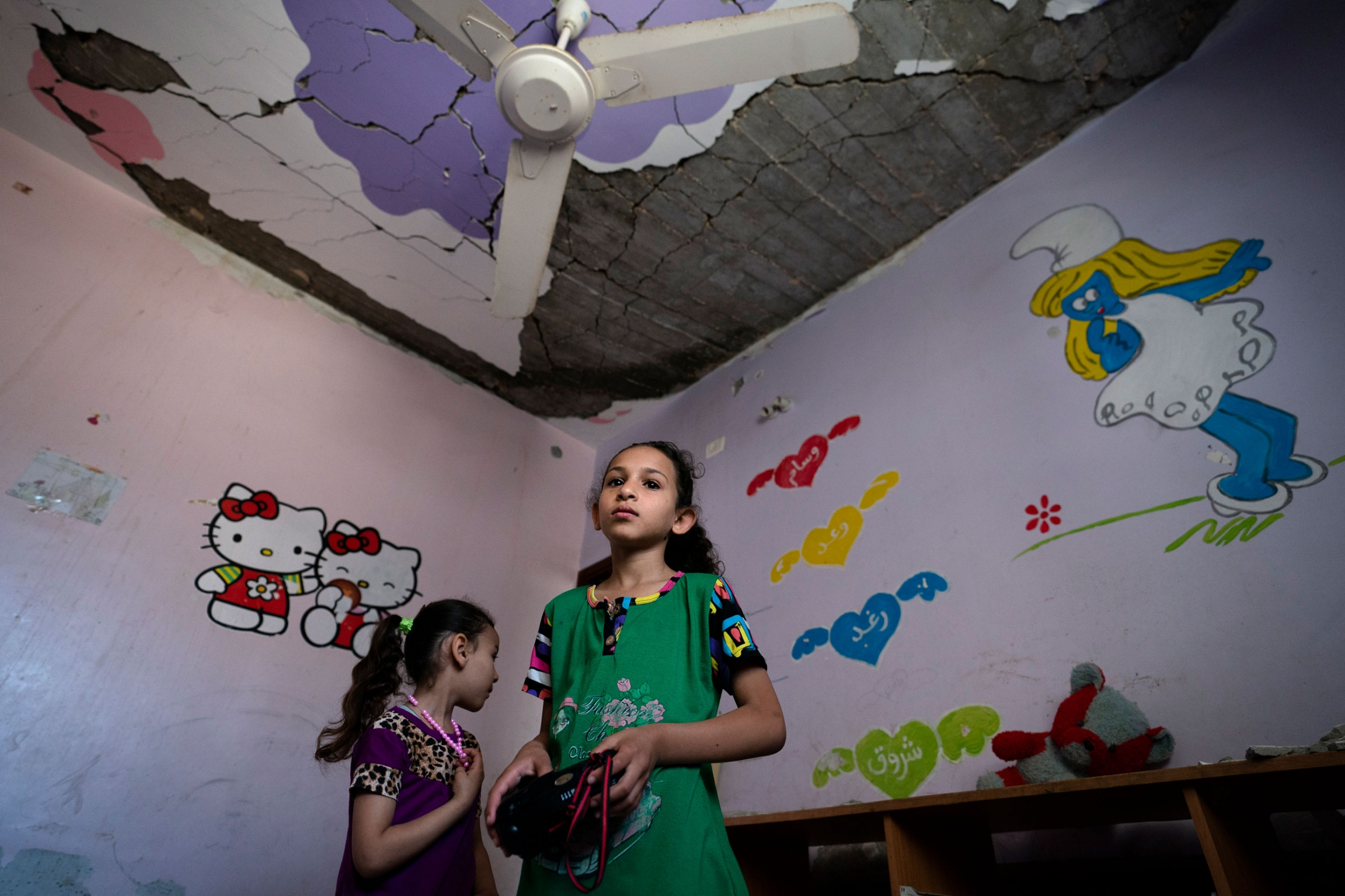 Two young girls are shown in a room with a smurf cartoon on the wall and a damaged ceiling.