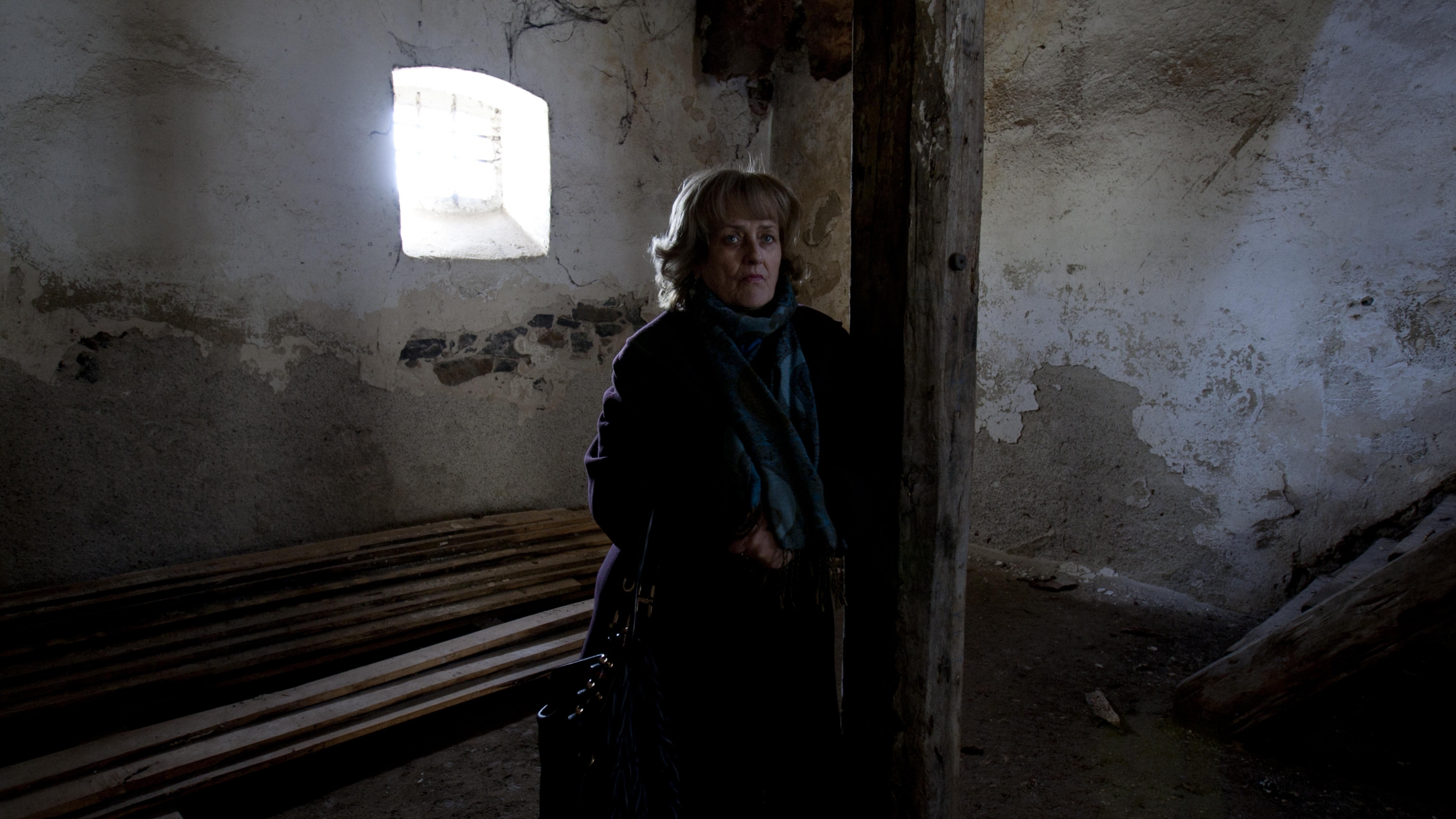 A woman stands in an abandoned building with light coming through the window.