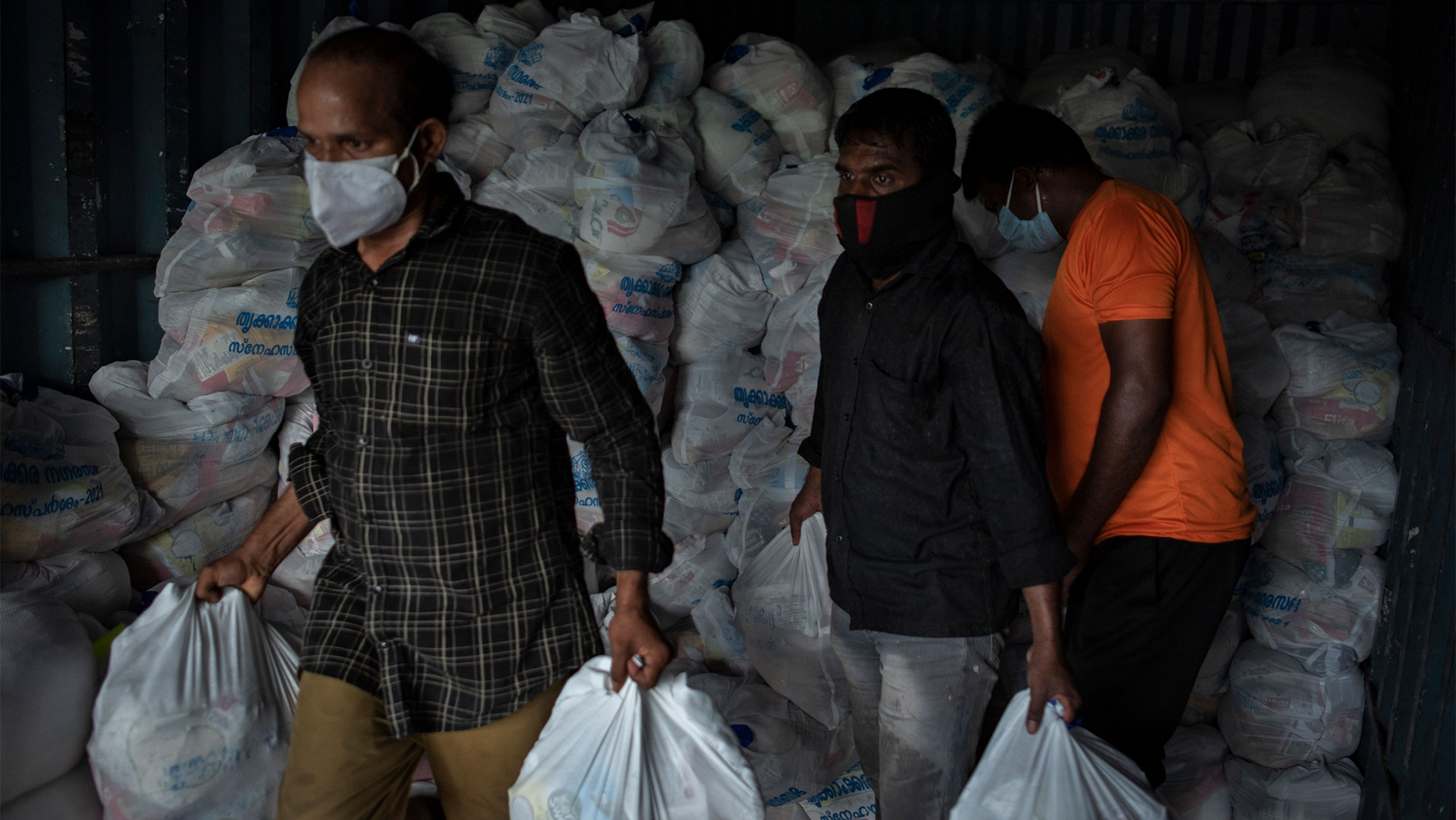 Men carrying white plastic bags of food from a pile of bags