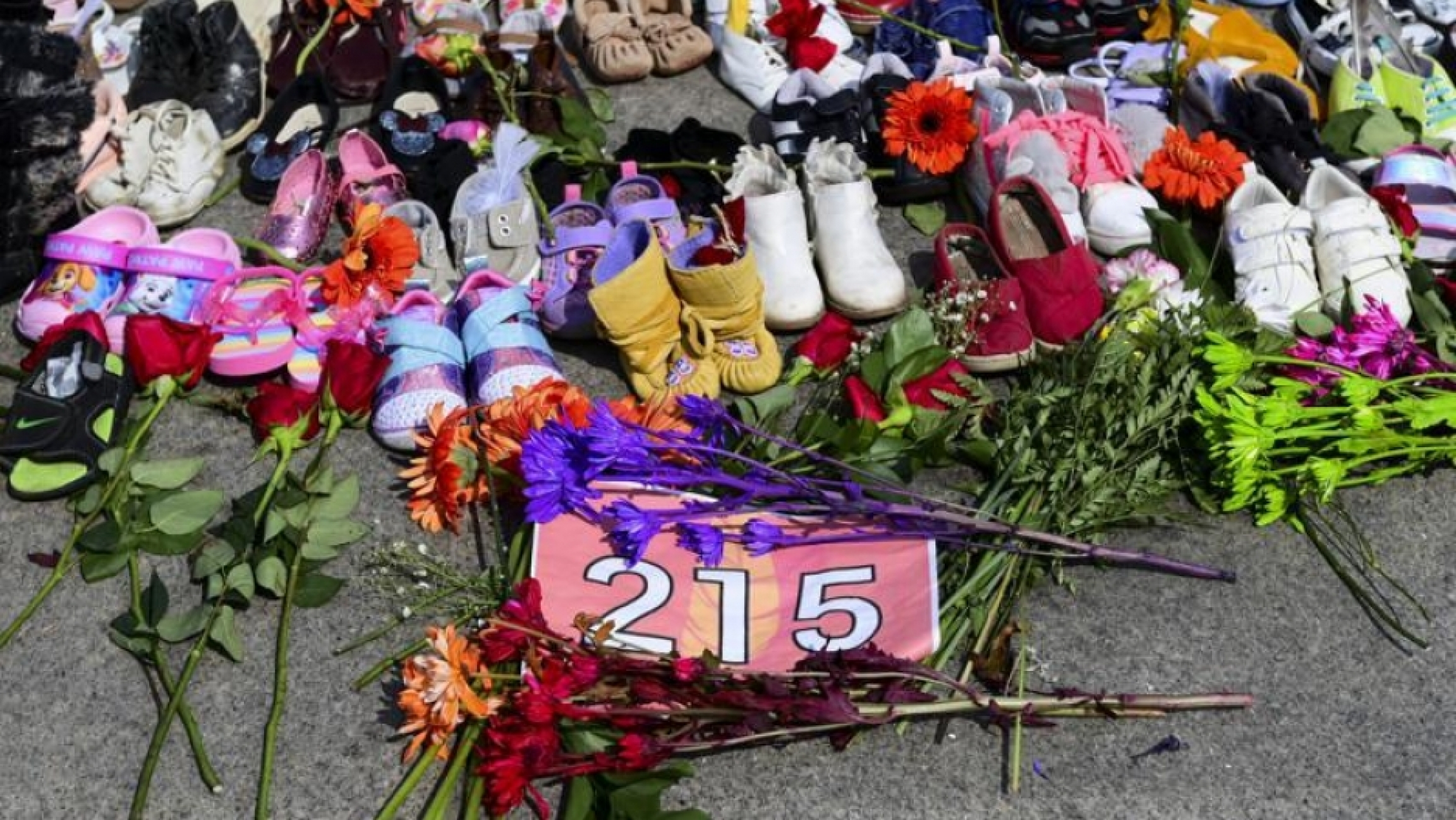 Flowers, children's shoes and other items rest at a memorial at the Eternal Flame on Parliament Hill in Ottawa