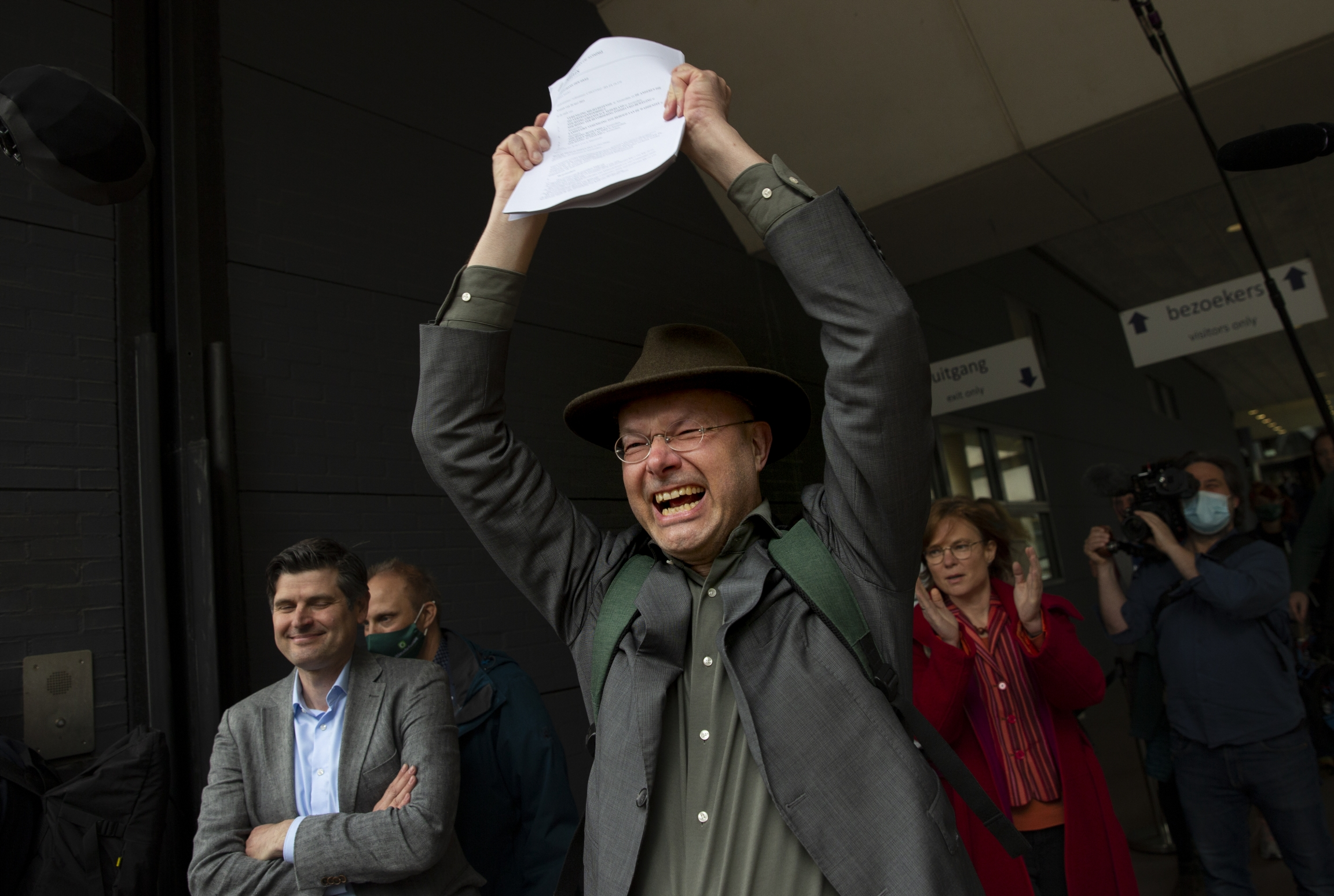 A man victoriously holds up a piece of paper and smiles as other people around him also smile