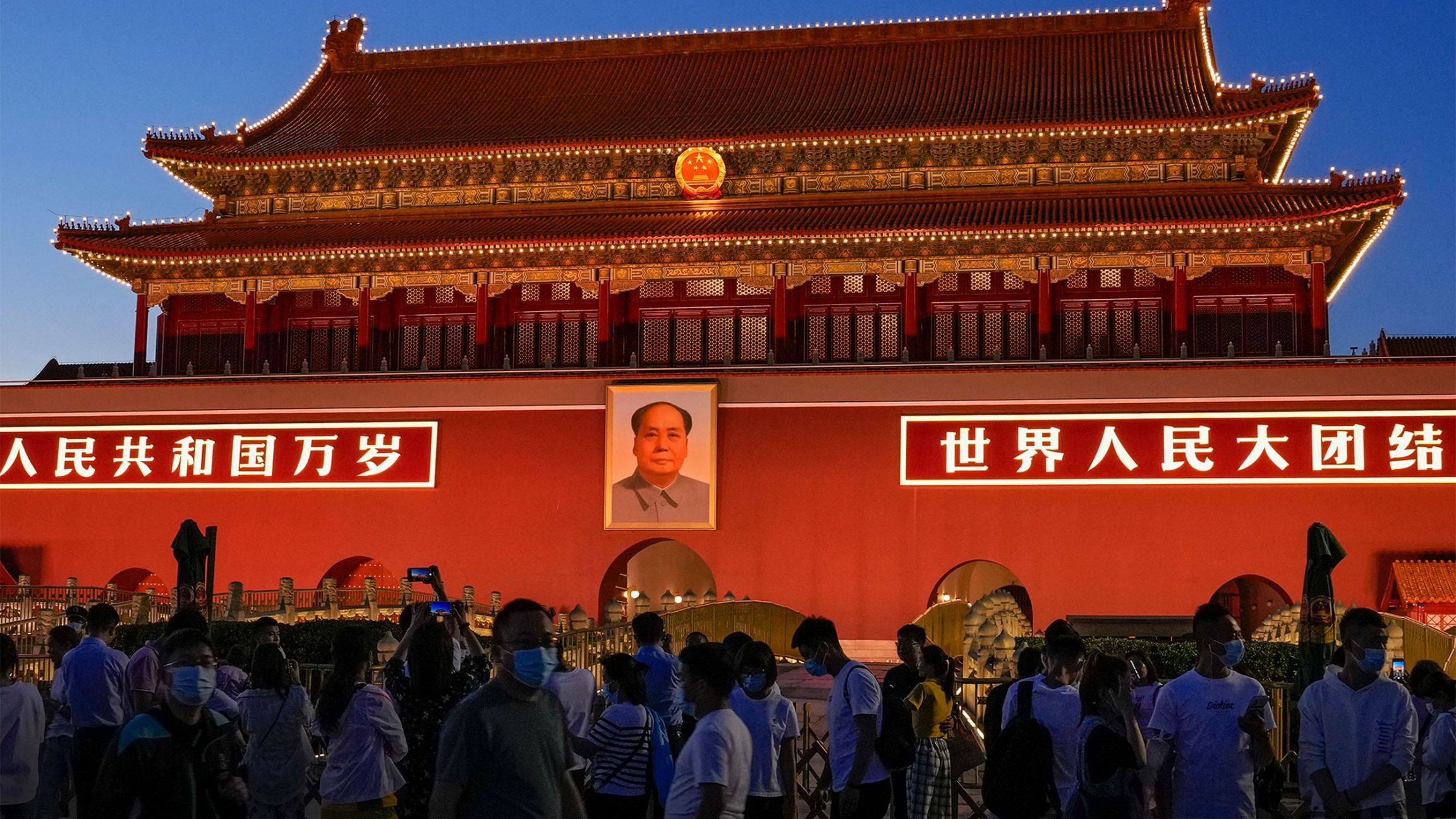 Red building in China with people in masks mingling in front of it