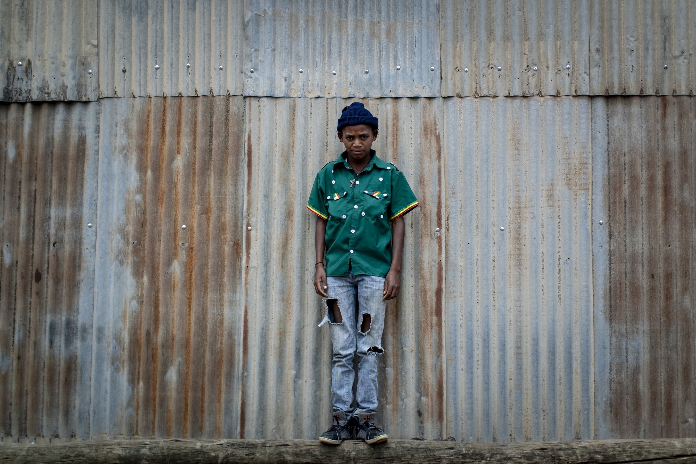 boy stands against corrugated steel wearing a green cultural shirt with buttons and jeans.