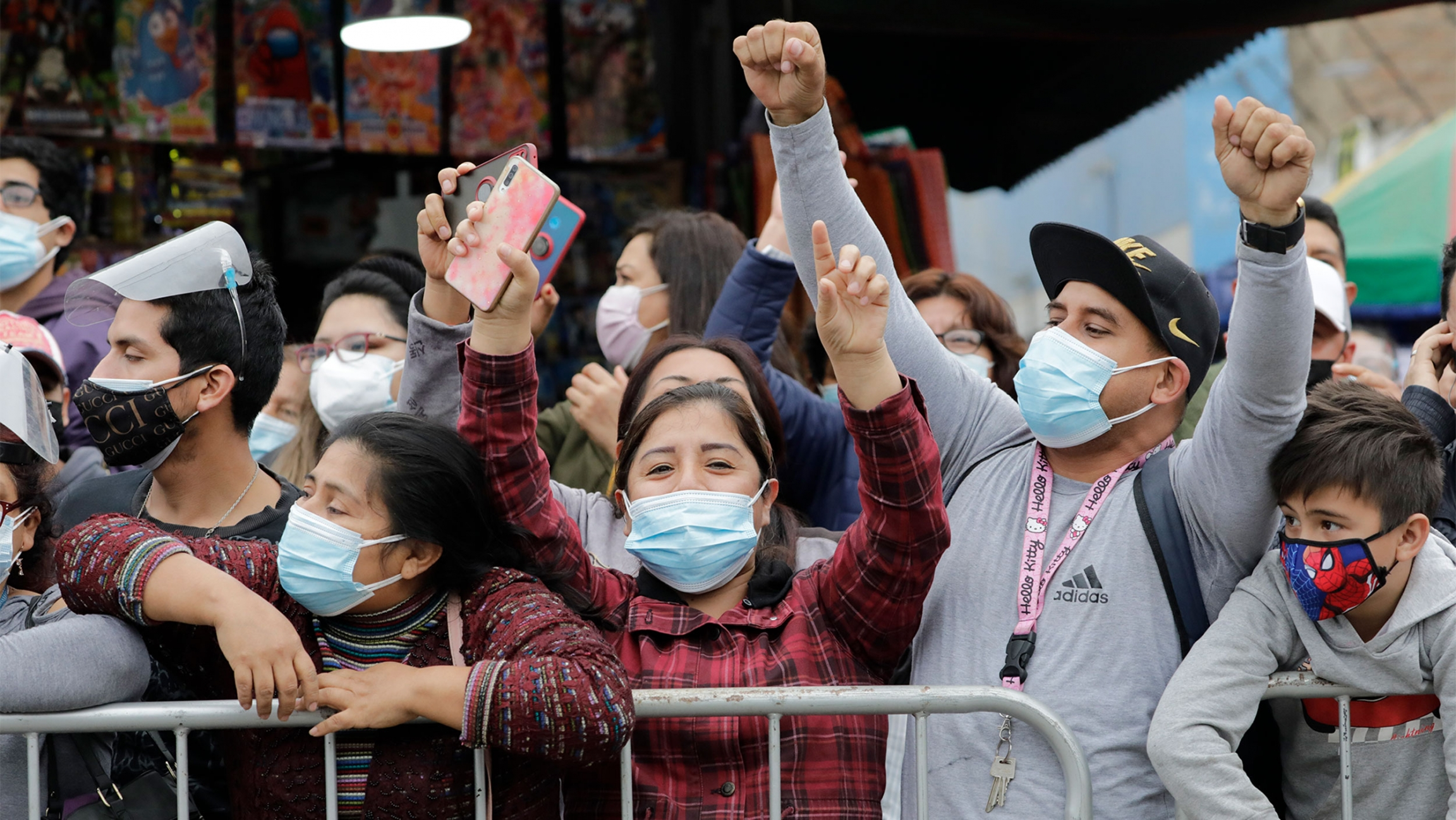 People wearing masks behind a barricade hold their hands and fists up in the air