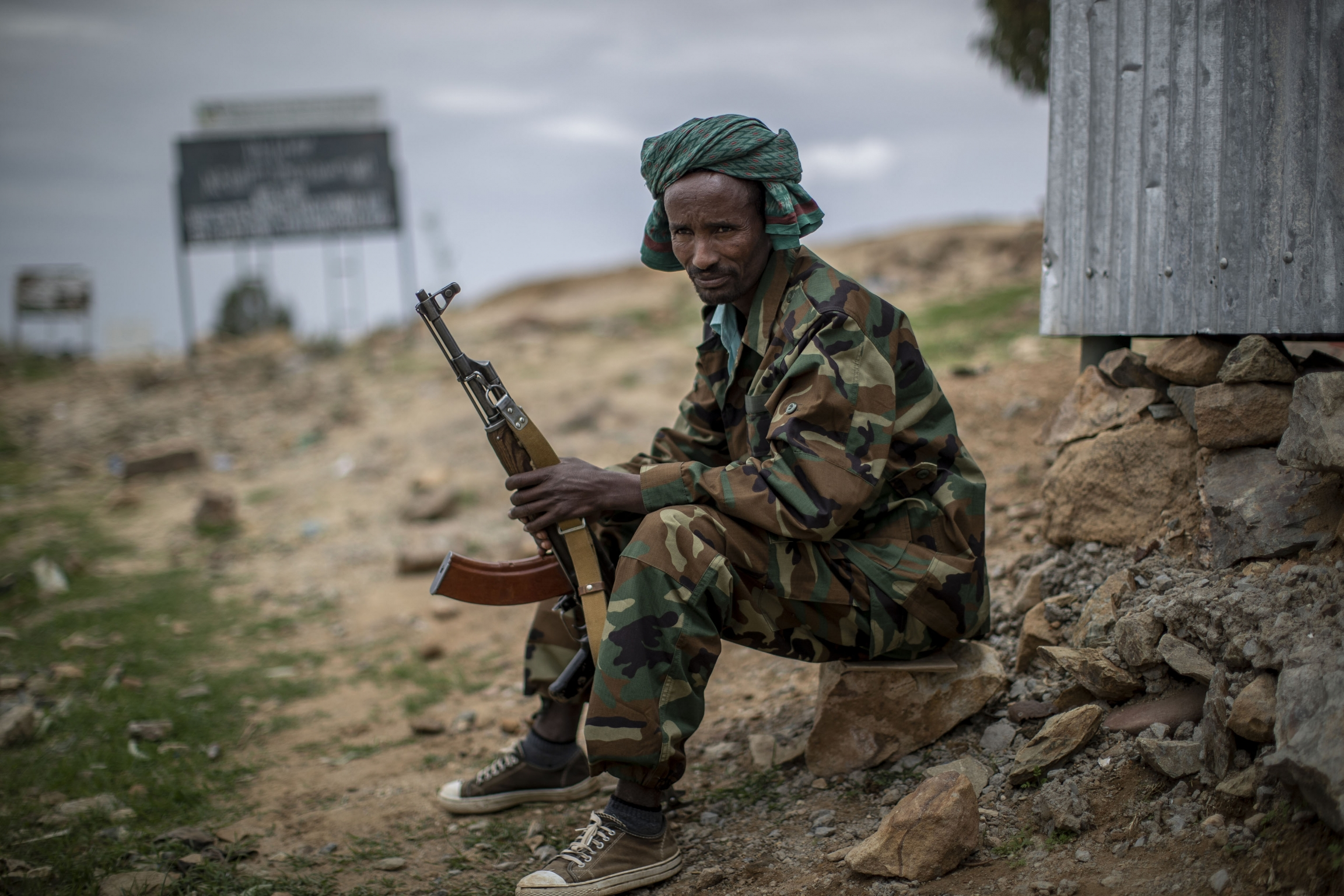 A soldier holds his gun while sitting done.