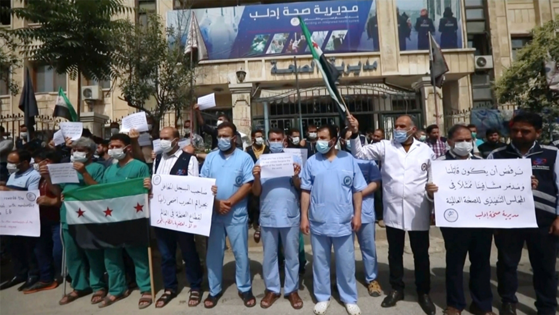 Doctors stand in front of a hospital holding signs