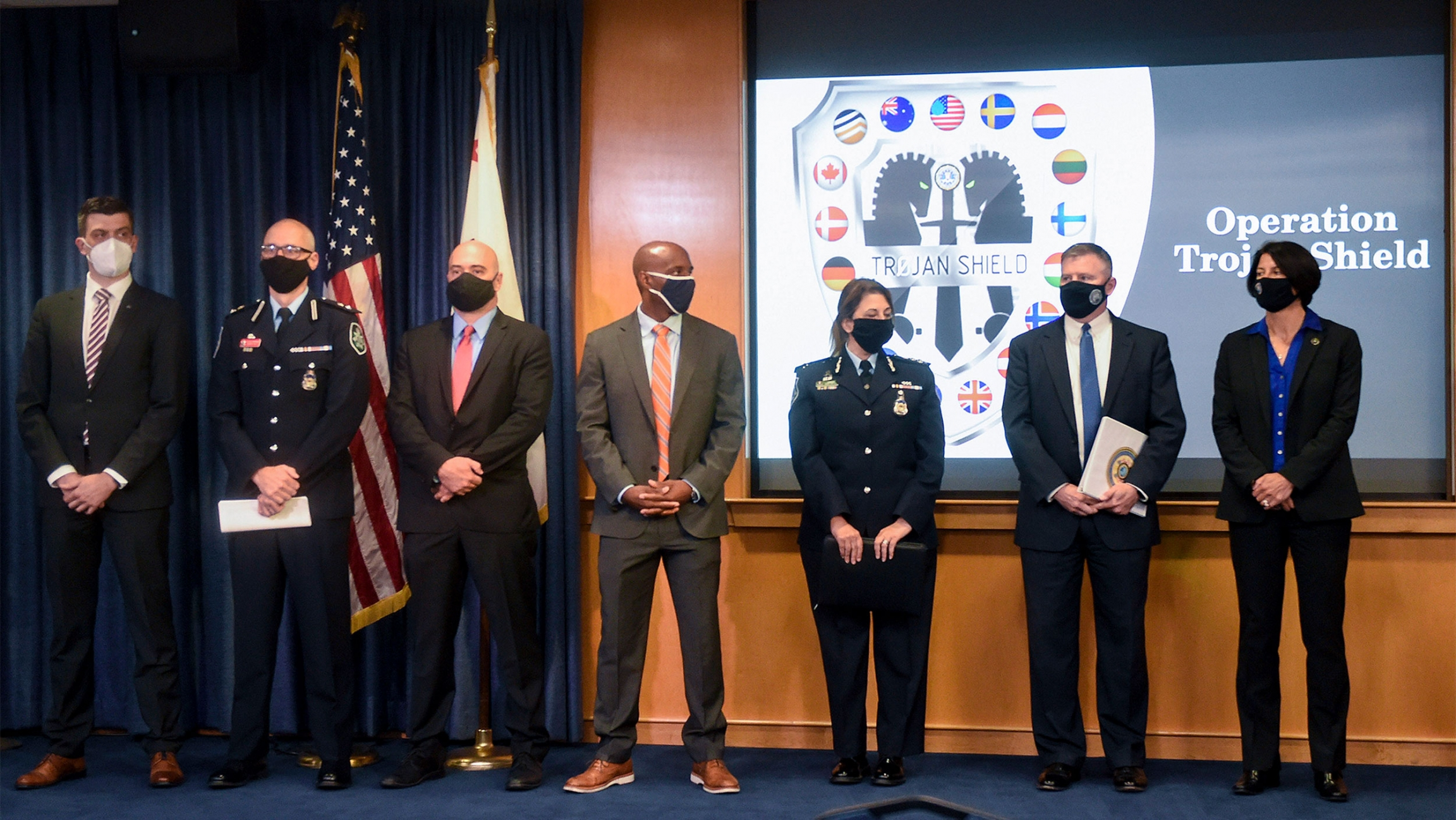 Law enforcement officials stand in front of an Operation Trojan Shield logo at a news conference