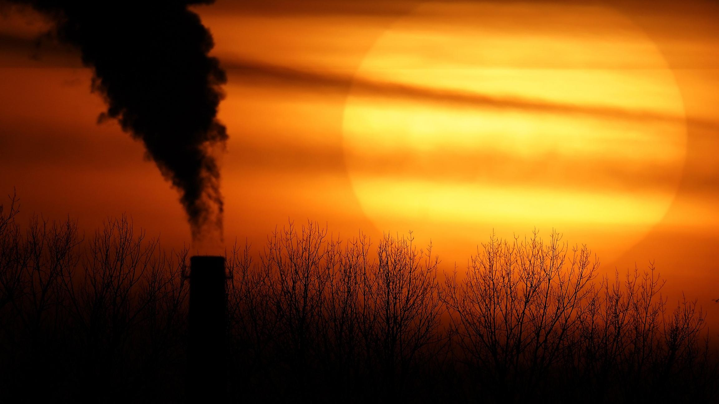 A setting sun near a smokestack.