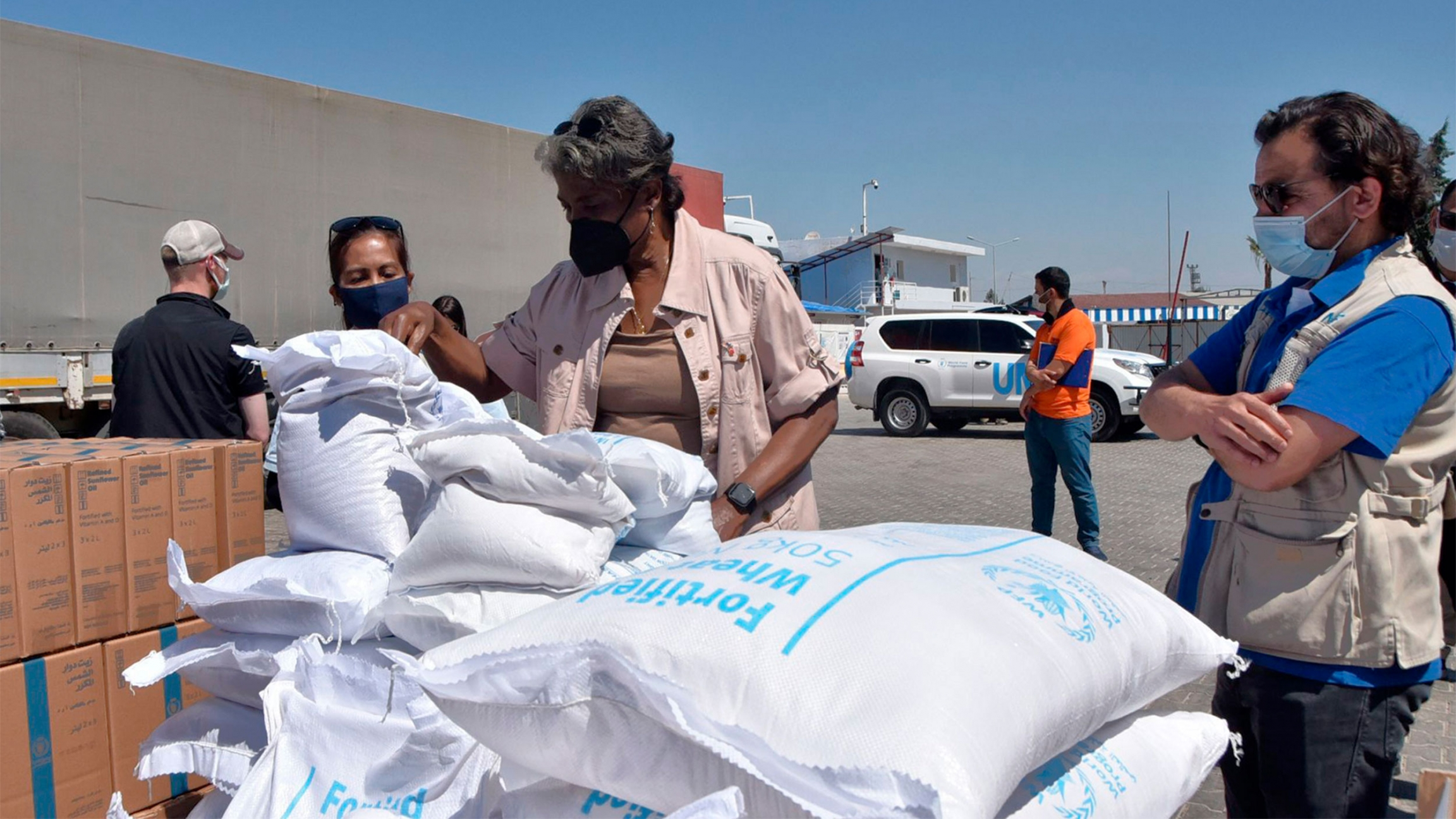 People wearing masks stand in front of white bags of food aid