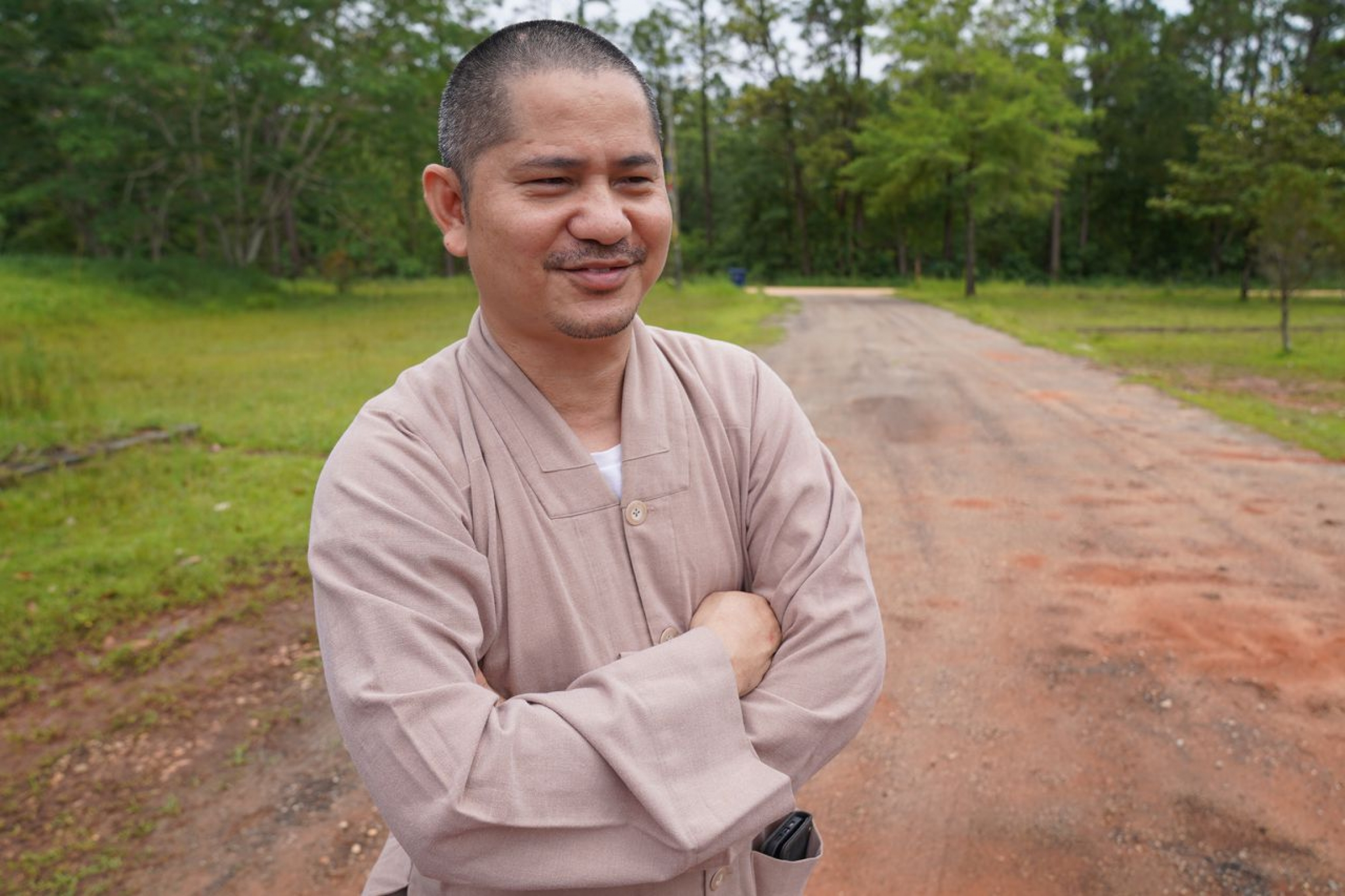 A man smiles while standing with his arms folded