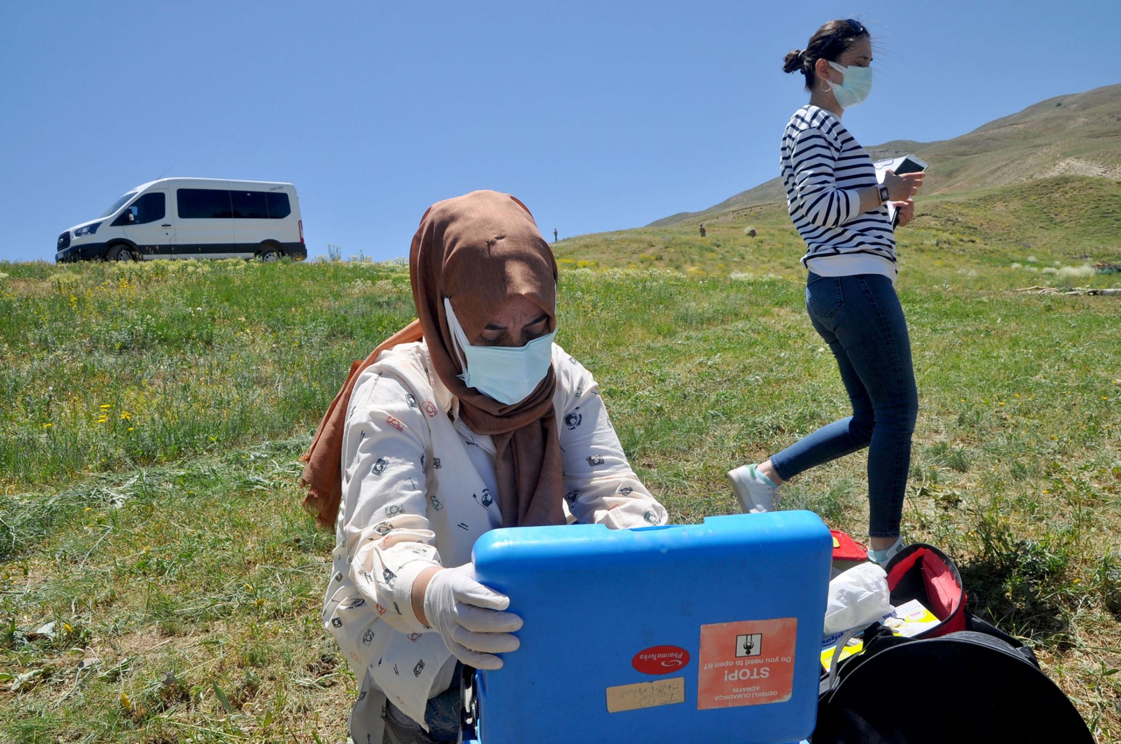 A health worker unloads equipment to vaccinate sheepherders in Ömerova, a village in Turkey's eastern Kurdish region.