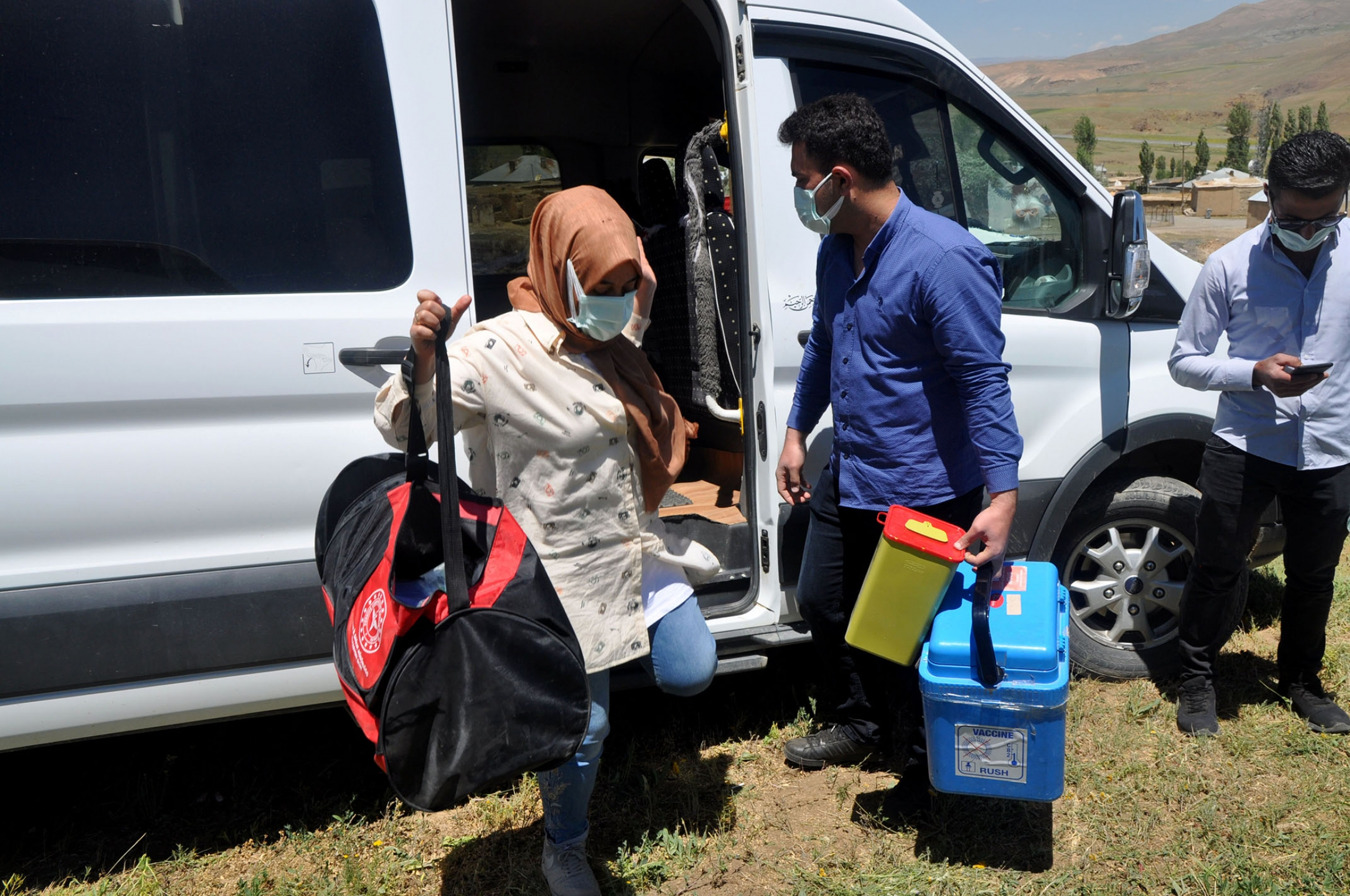 Health workers unload equipment to give out COVID vaccines in Ömerova, a village in Turkey's eastern Kurdish region.