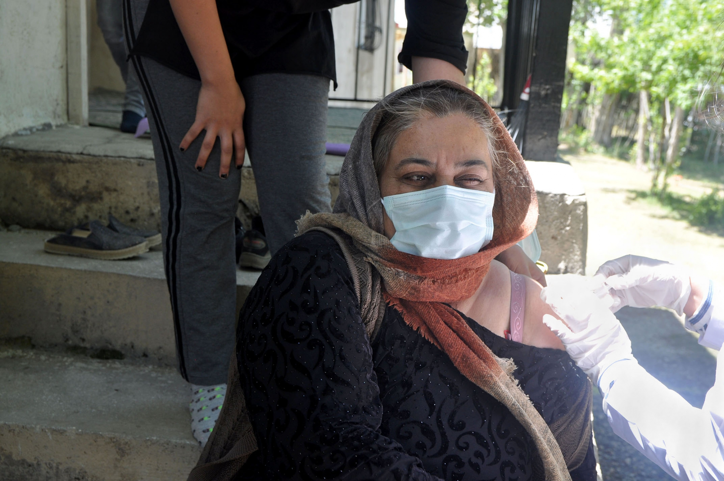 Emine Saruhan winces during a COVID vaccination shot on her front porch in the town of Ömerova. The 46-year-old has a health condition, and hoped a vaccine would alleviate some of her fears.