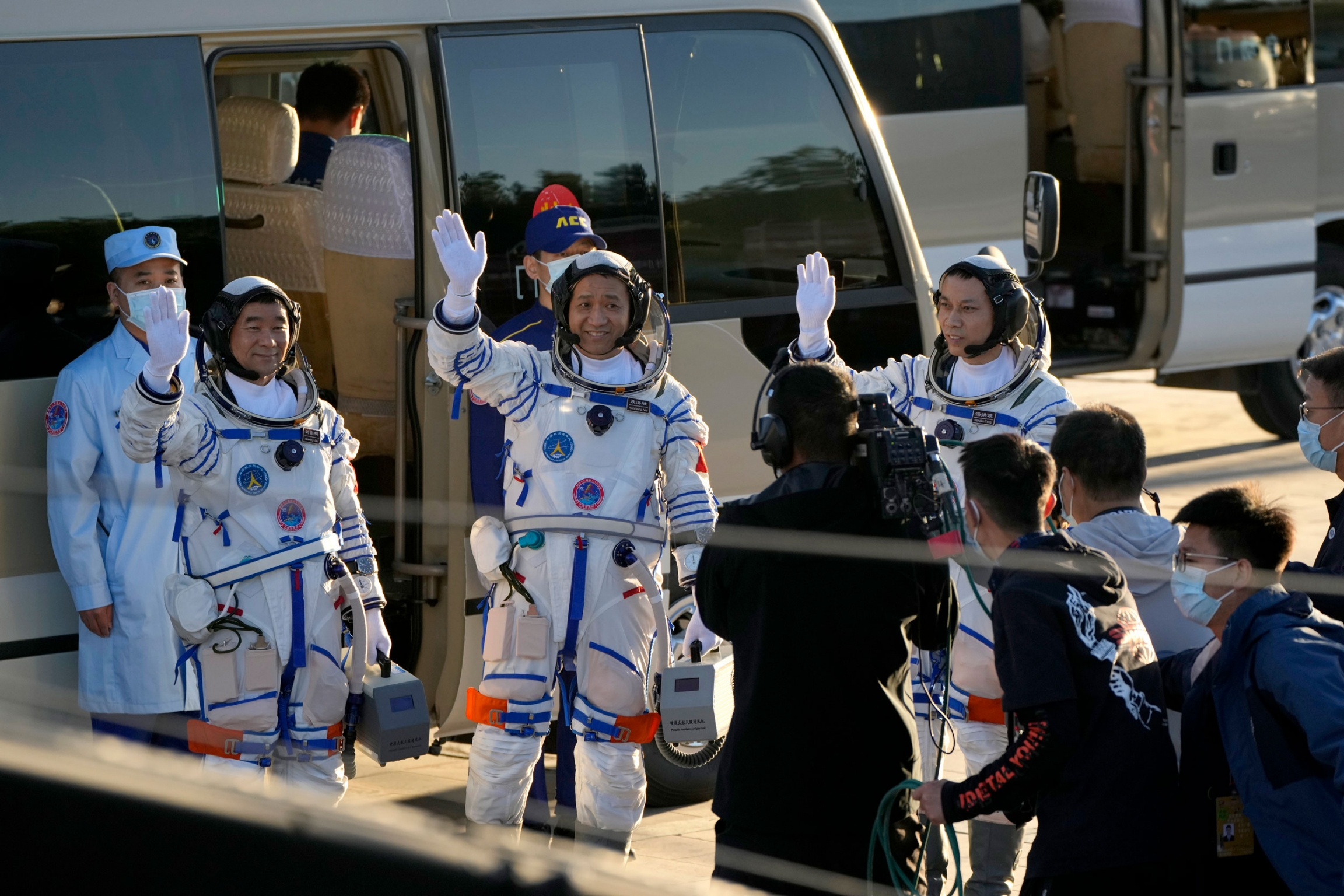 Chinese astronauts are shown wearing white and blue stripped space suits and waiving.