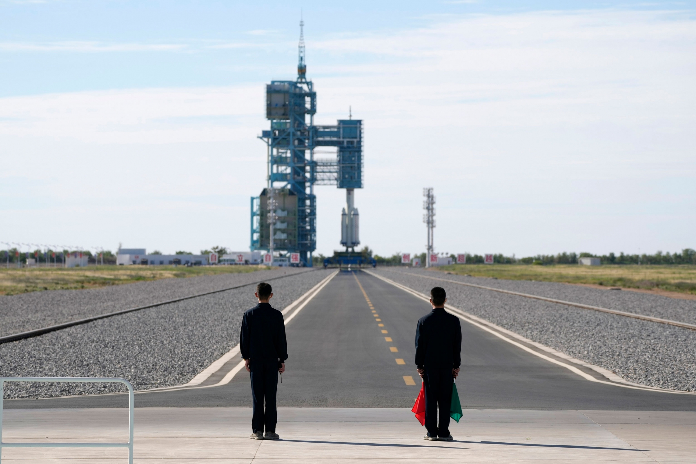 Two people are shown at the end of a long tarmac with the Chinese spaceship set for launch in the distance.