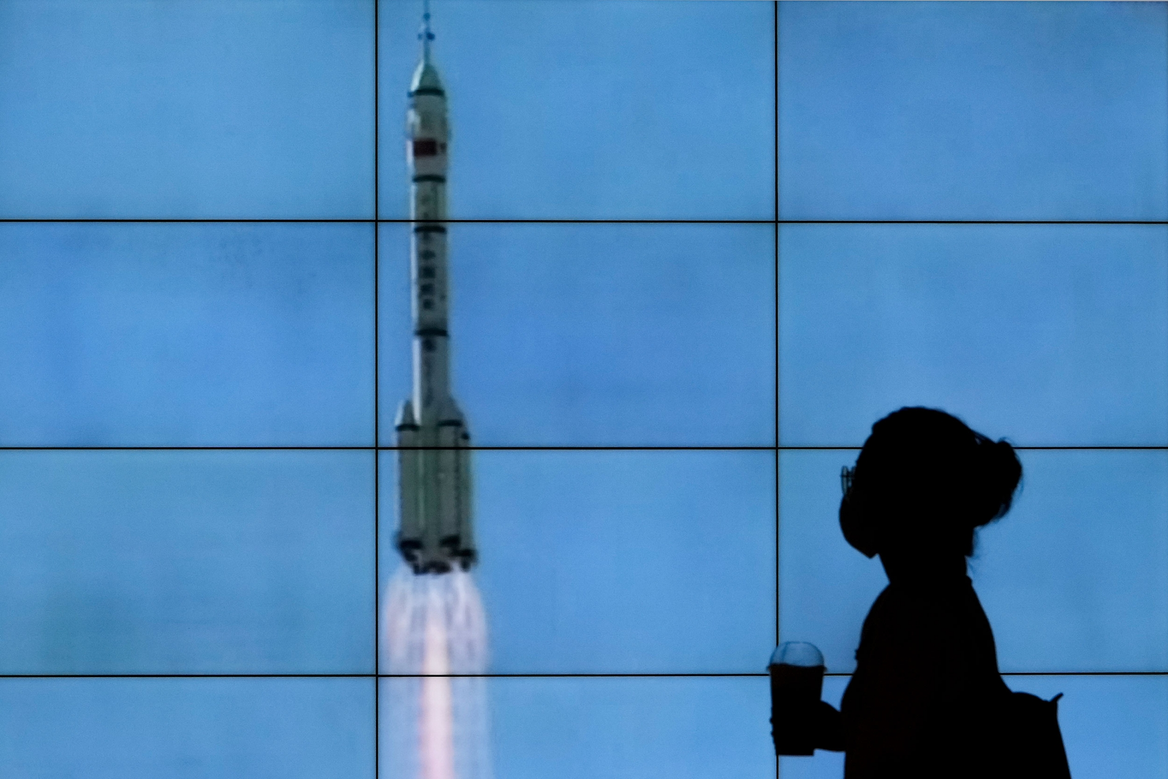A woman is shown in shadow standing in front of a screen showing the Chinese spacehip lifting off.