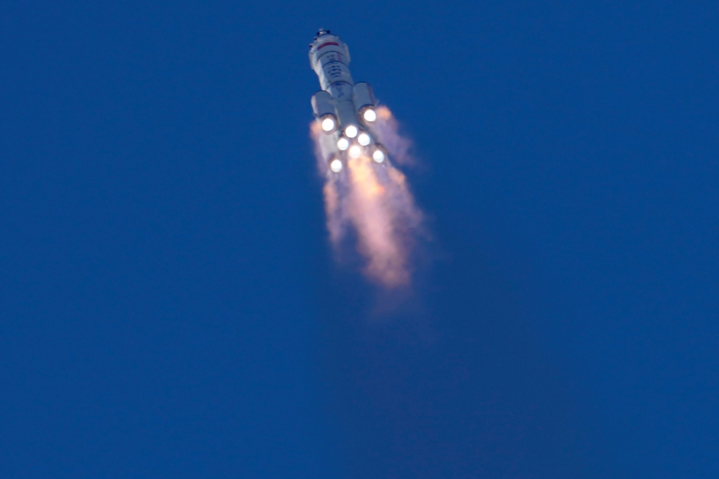 The firey bottom of eight rockets are shown from below lifting the Chinese spaceship into the sky.