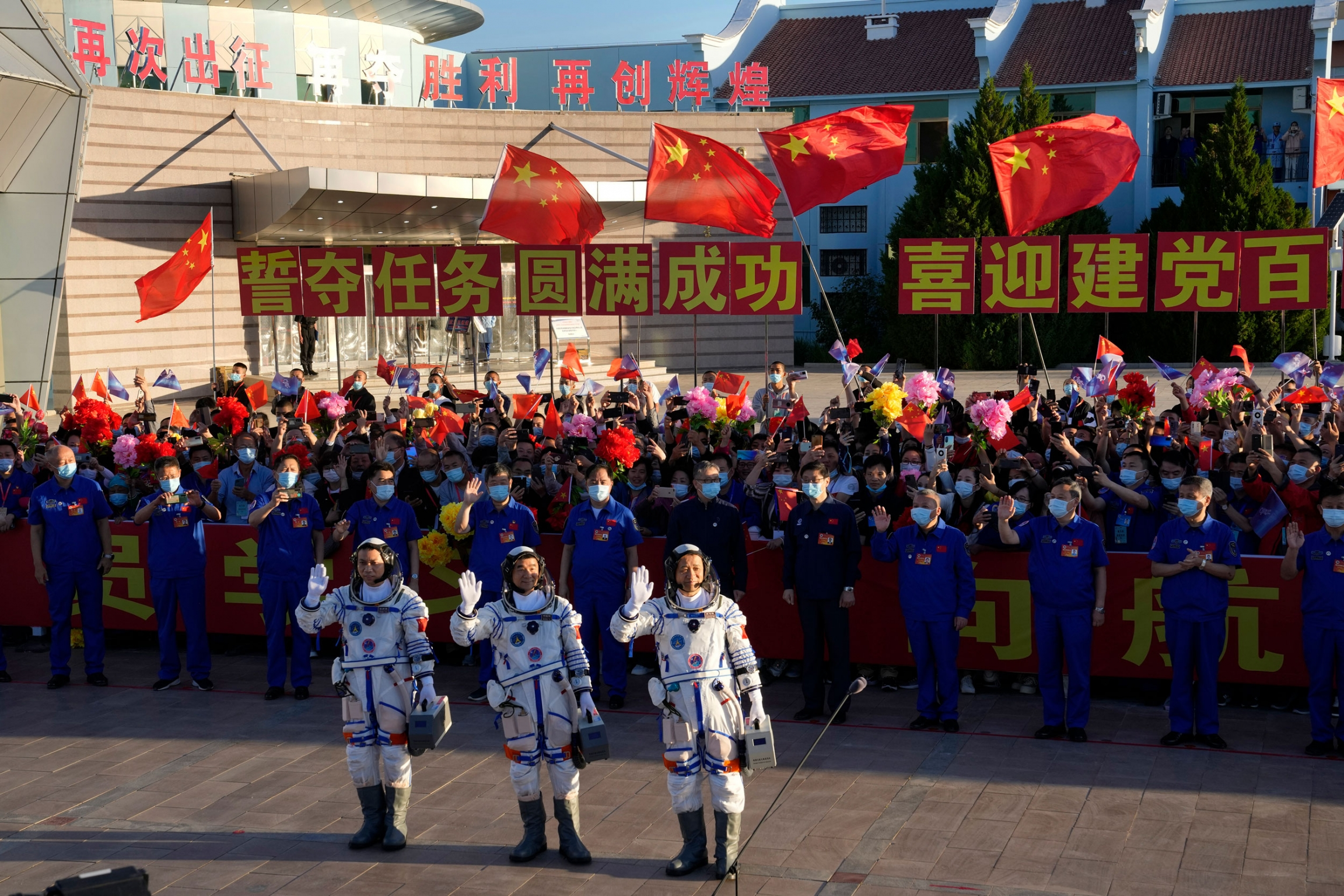 Three Chinese astronauts are shown waving with a large crowd of people waving the Chinese flag behind them.