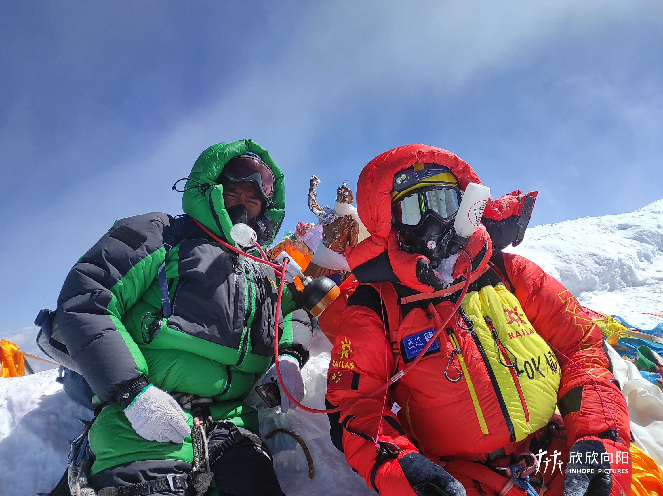 Two men wearing green and red coats stand amid a snowy Mount everest