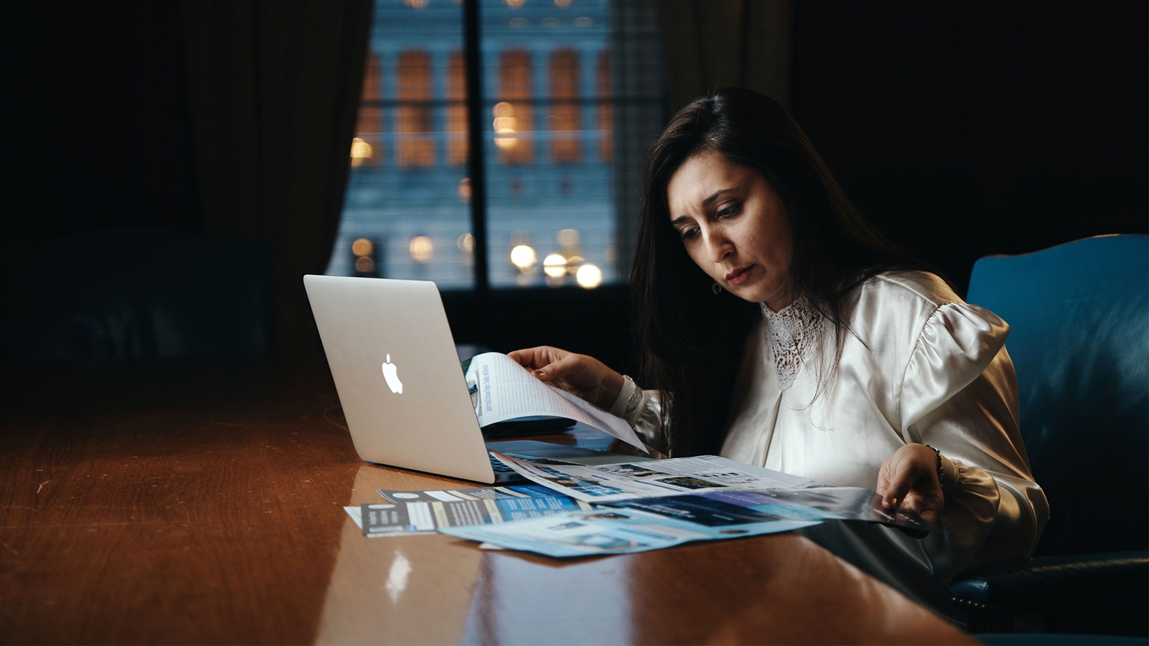 Woman in a white blouse working at a desk on her laptop