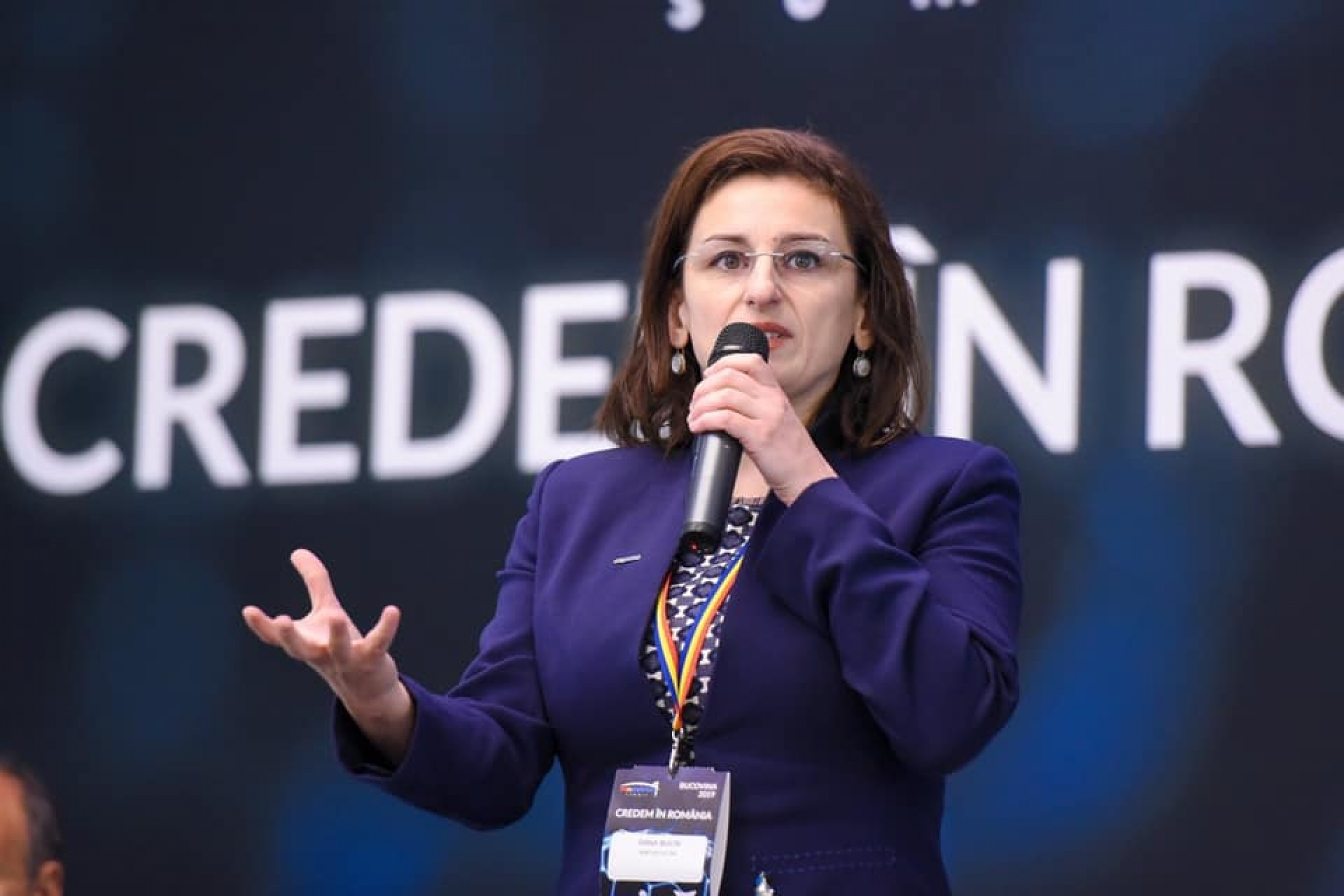 Woman in purple suit speaks with a microphone