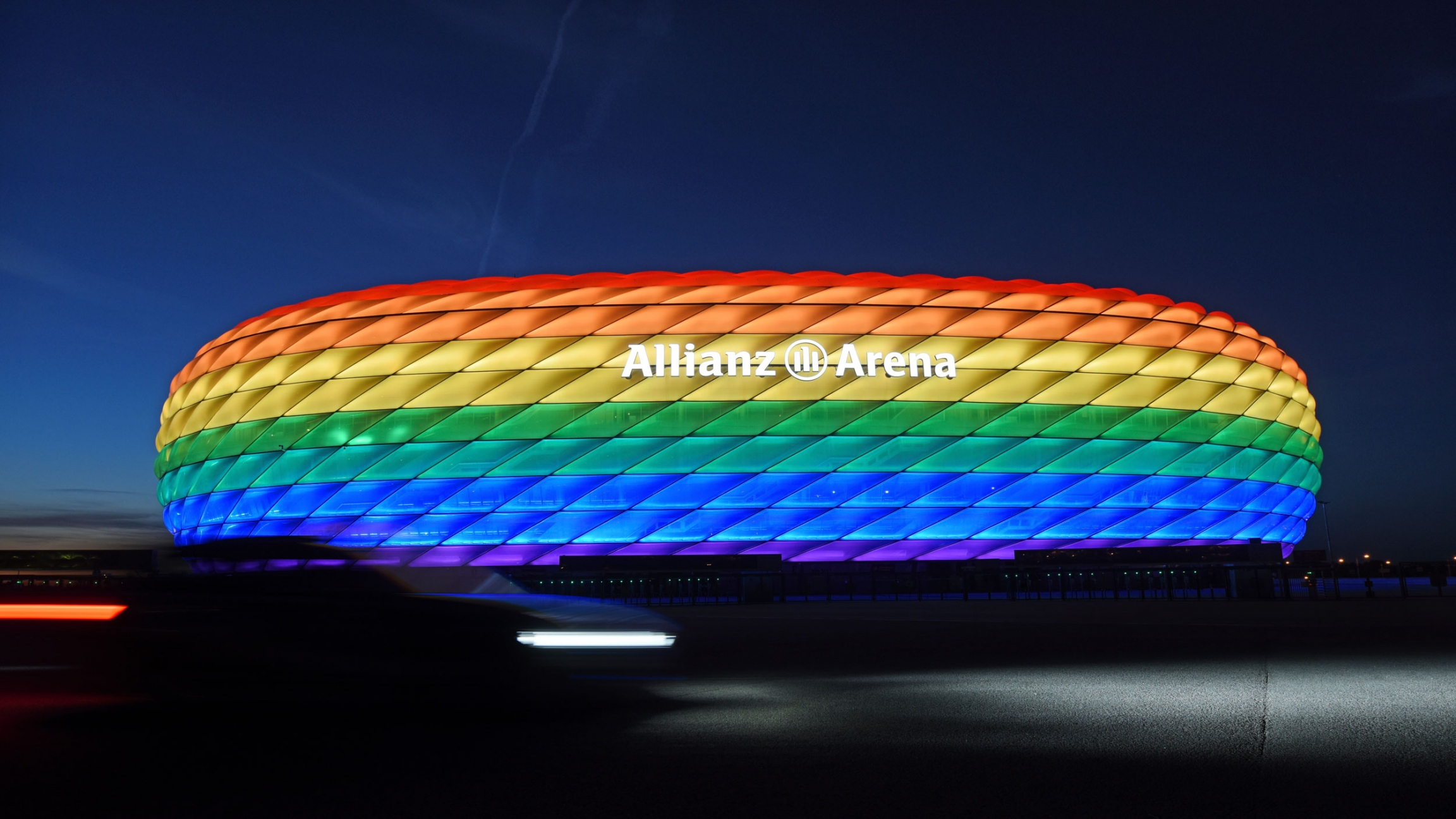 The Allianz Arean in Munich is shown illuminated in the colors of the rainbow with the night sky in the background.