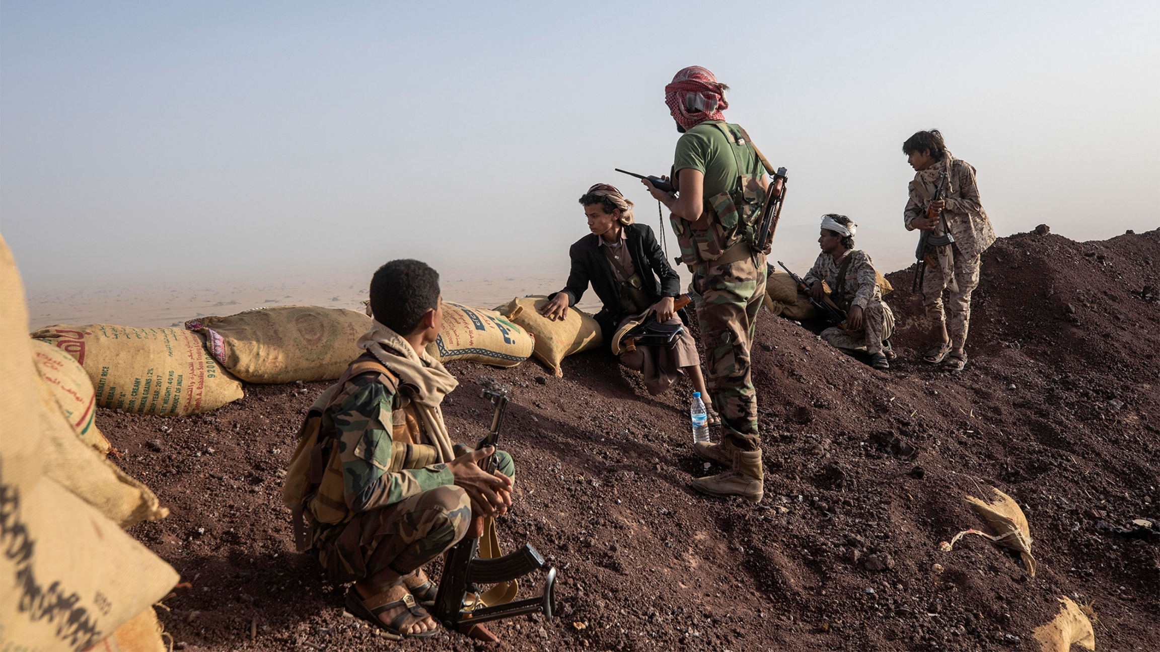 Yemeni fighters look over a mound of soil lined with sandbags