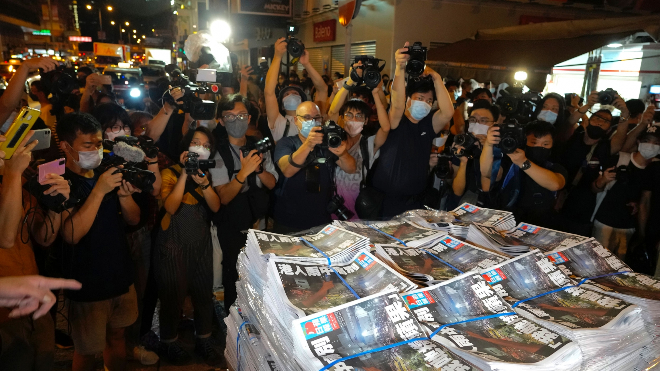 Several stacks of the last edition of the Apple Daily newspaper are shown a group of photographers in the background.